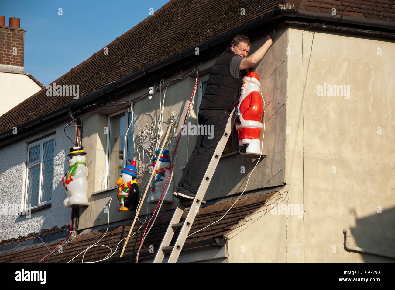 Hanging Christmas Decorations Outside.Man Up Ladder Hanging His Christmas Decorations Outside His