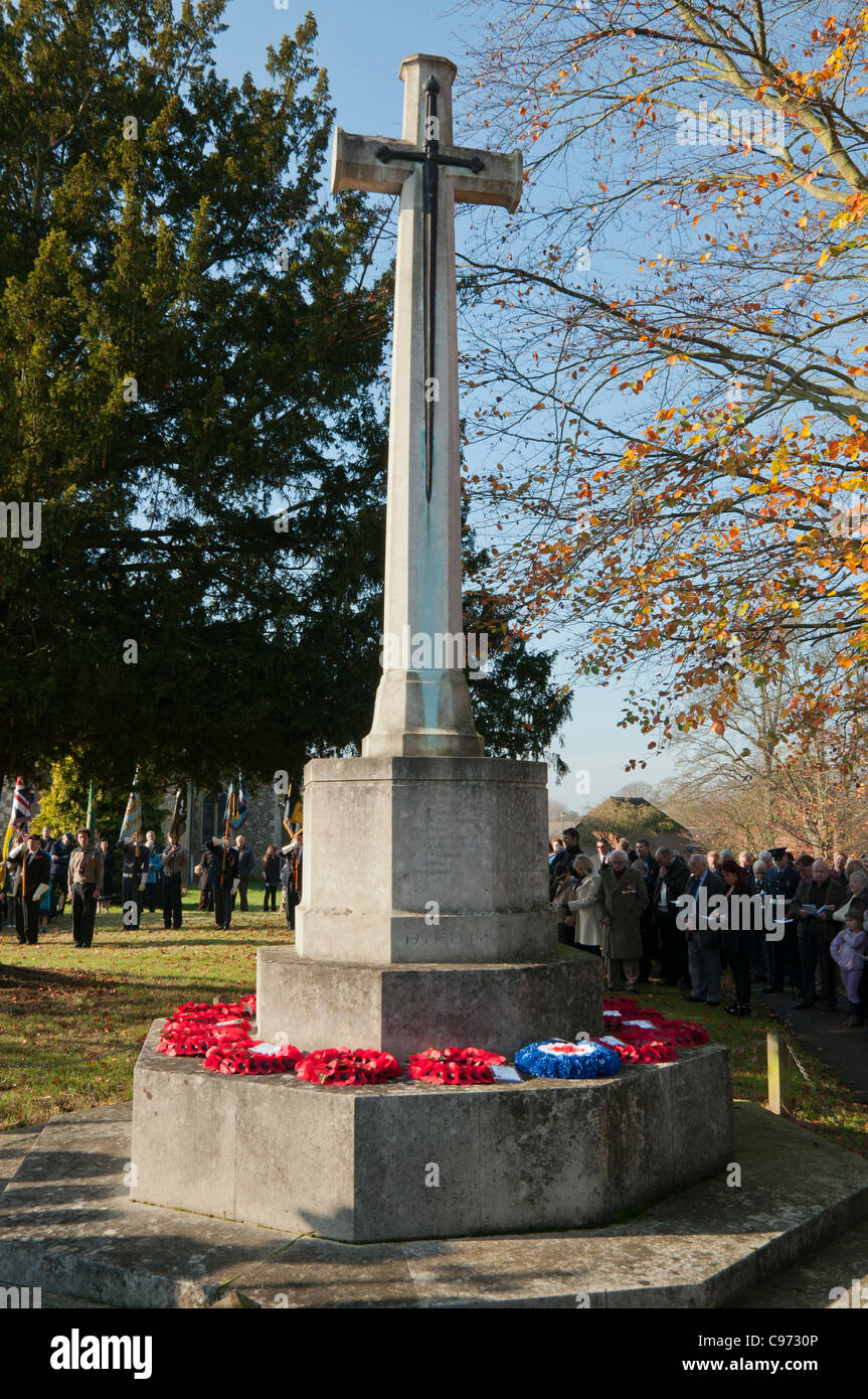 Remembrance day poppy wreaths on a war memorial in the grounds of St Lawrence church Abbots Langley Herts UK - Stock Image