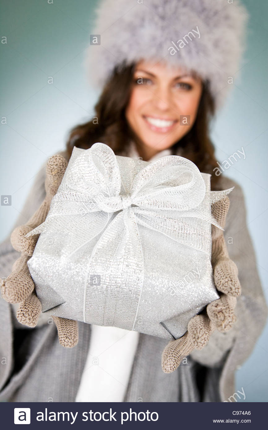 A young woman holding a Christmas present - Stock Image