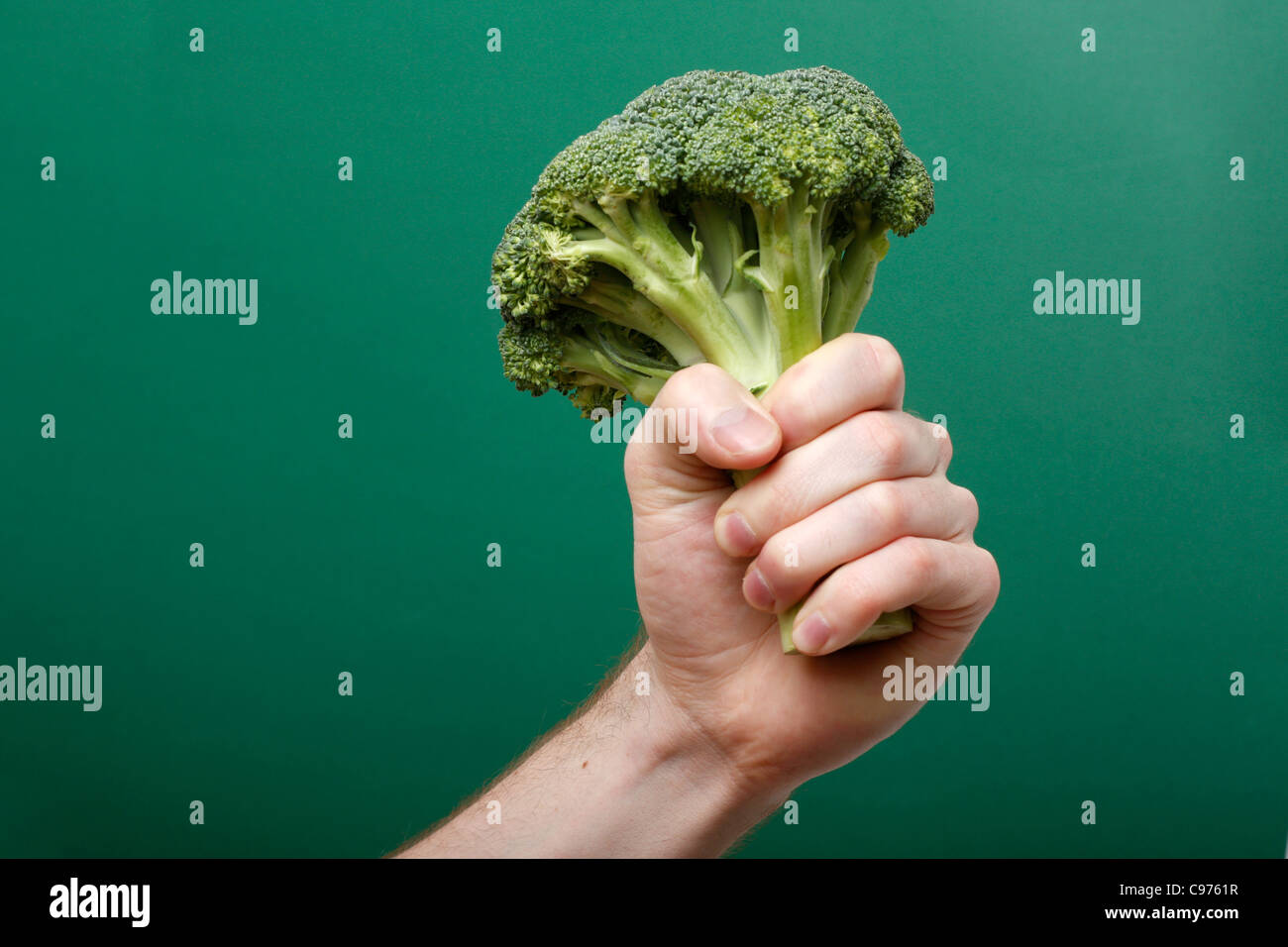 A hand holding broccoli - Stock Image