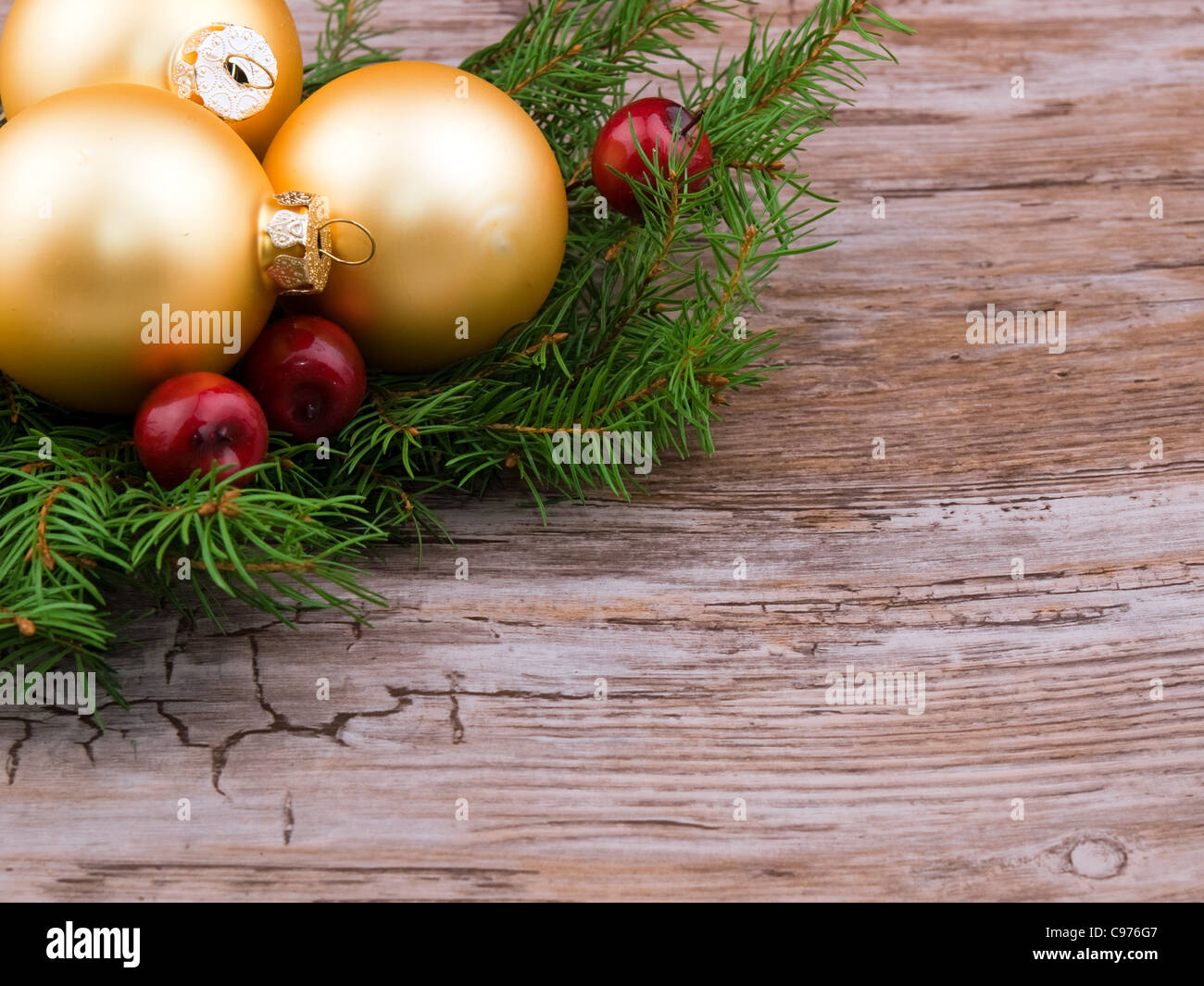 Golden christmas ball with fresh spruce branch on old wooden background - Stock Image