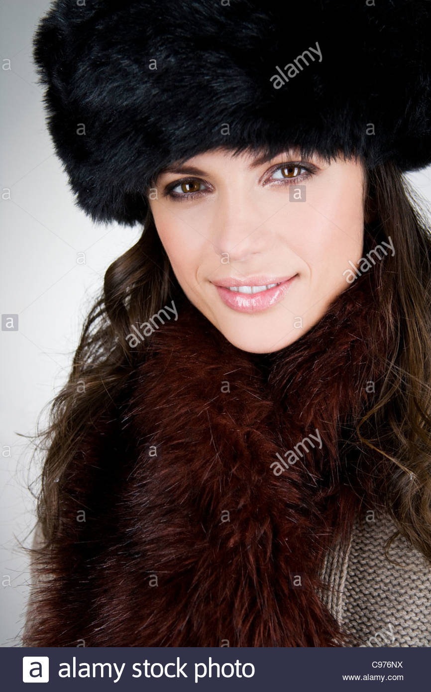 A young woman wearing a fur hat, smiling - Stock Image