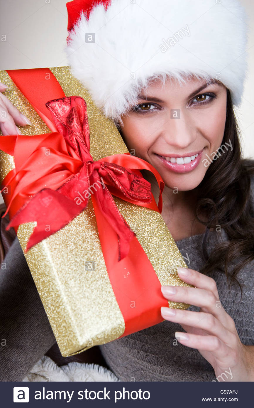 A young woman wearing a Santa hat, holding a Christmas present - Stock Image