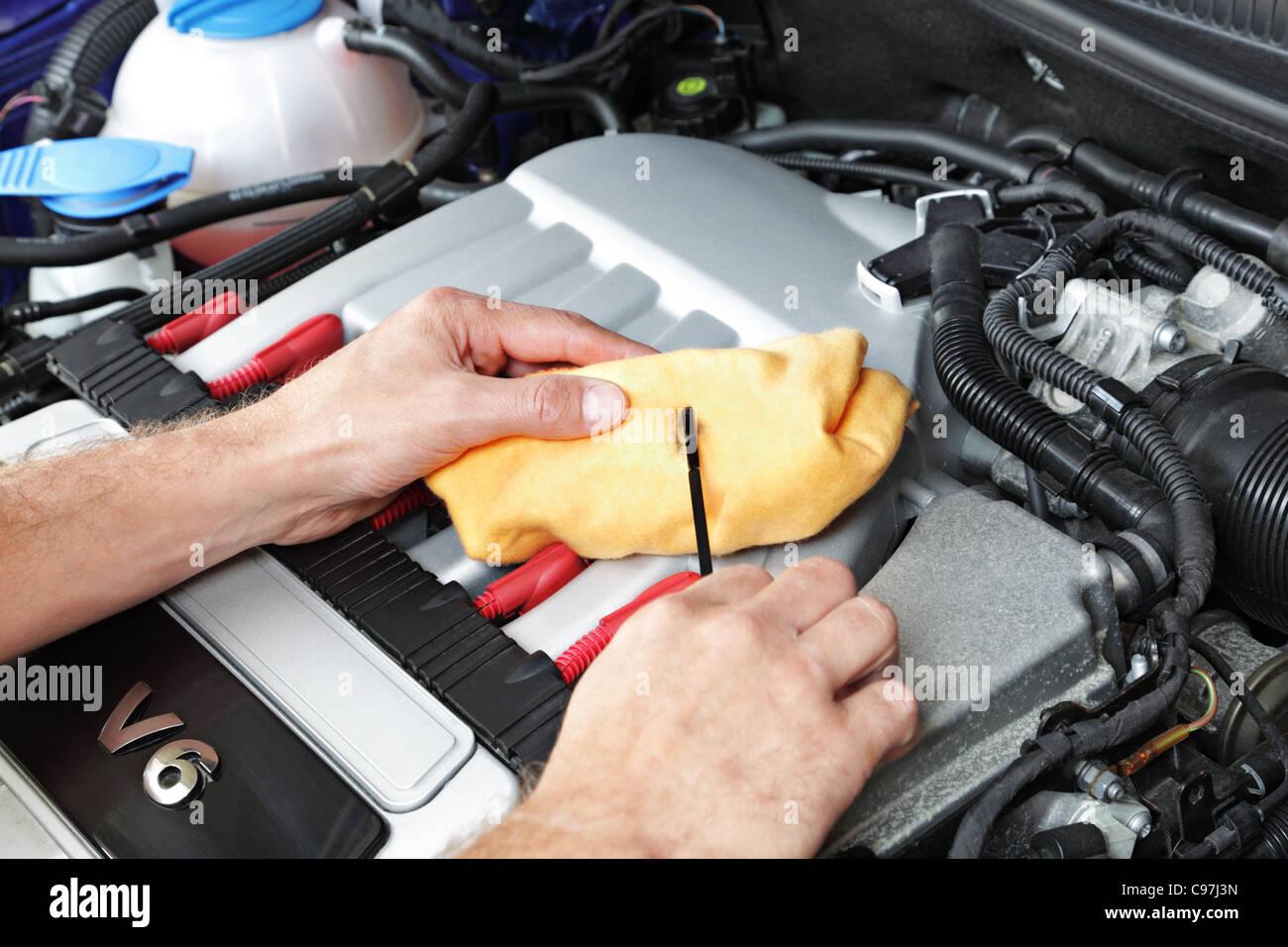 Mechanic checking motor oil - Stock Image