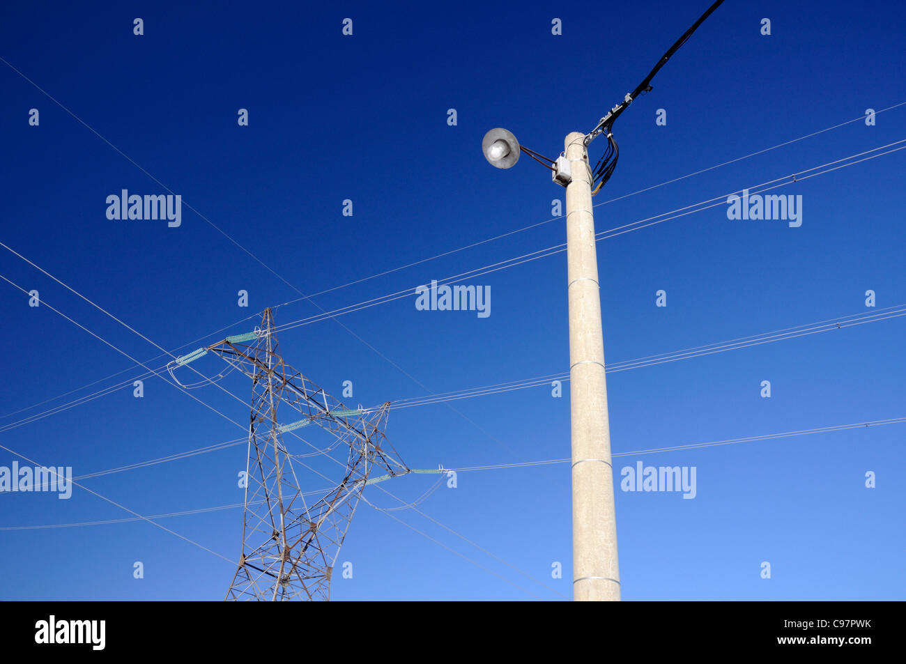 Power pylon and street lamp against blue sky - Stock Image