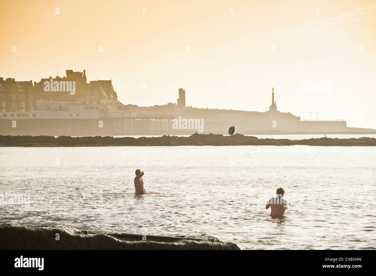 Two male university students playing in the sea enjoying a warm November afternoon, Aberystwyth Ceredigion Wales - Stock Image