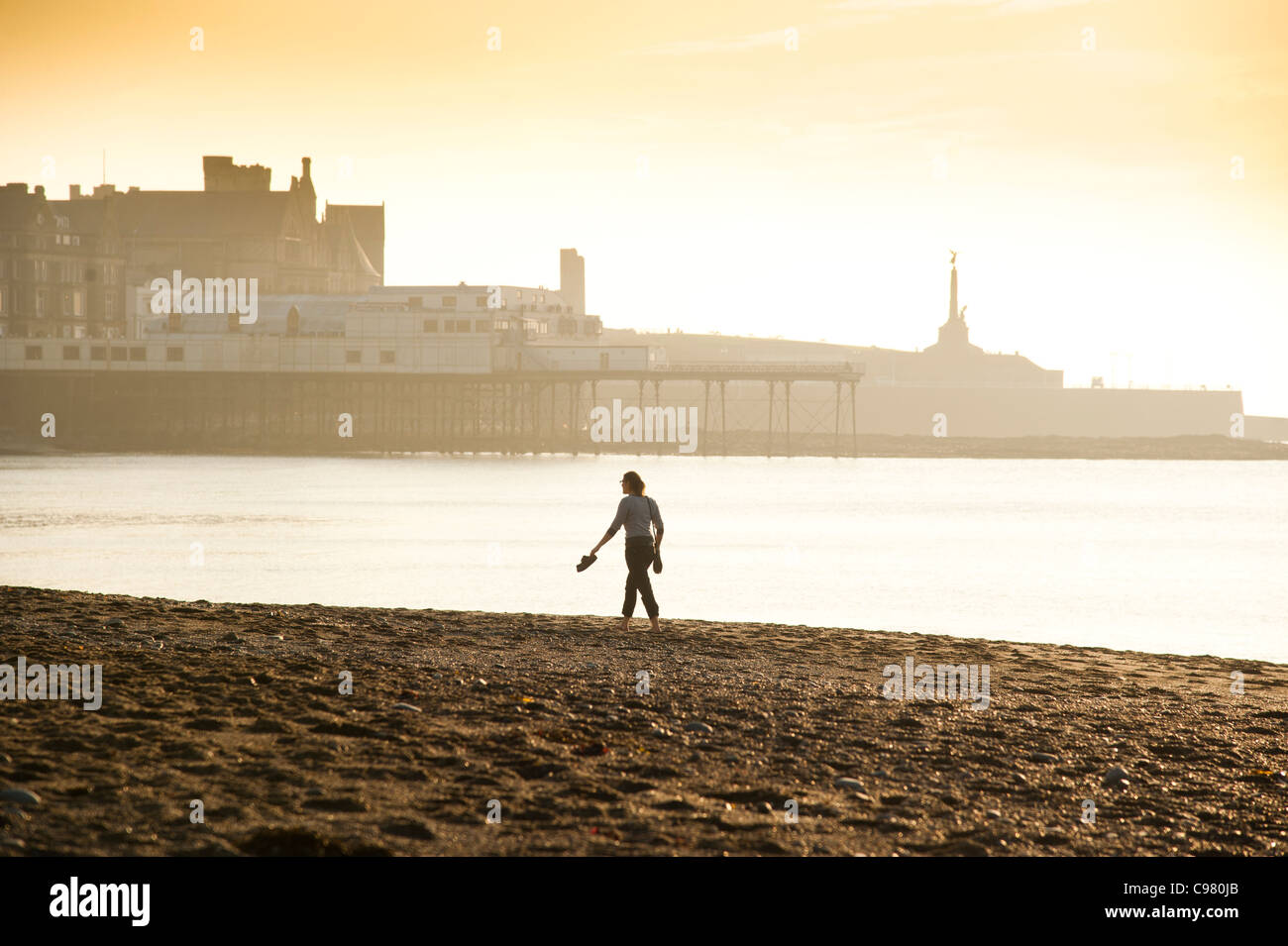 A woman walking barefoot on the beach enjoying a very warm November afternoon, Aberystwyth Ceredigion Wales UK - Stock Image