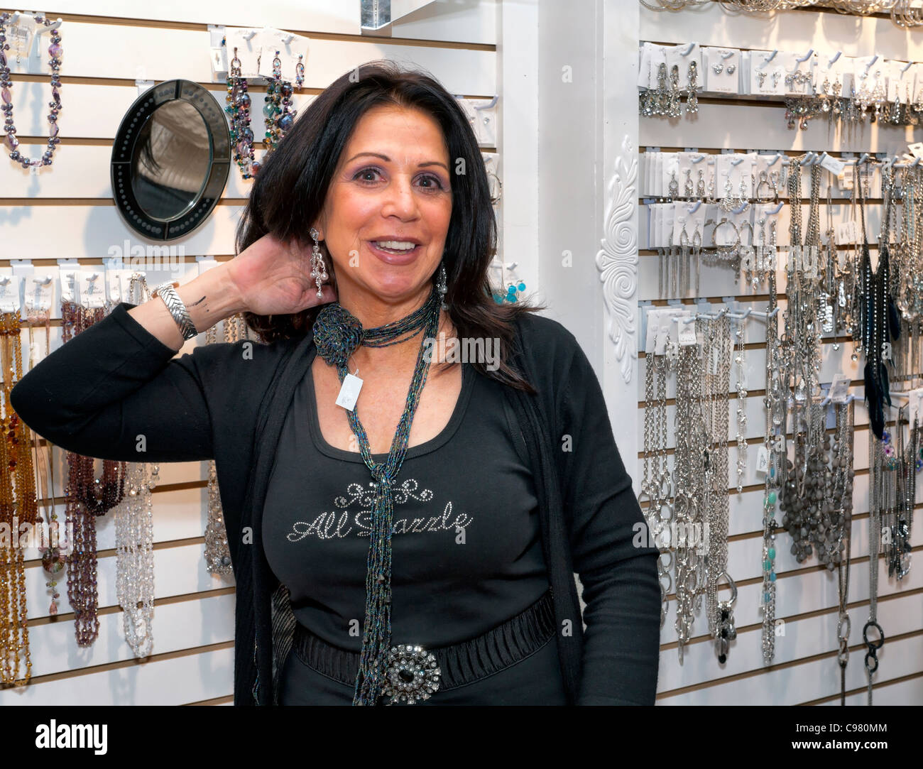 Saleswoman owner of fashion jewelry store showing earrings and necklace she's wearing, All Dazzle, Merrick, - Stock Image