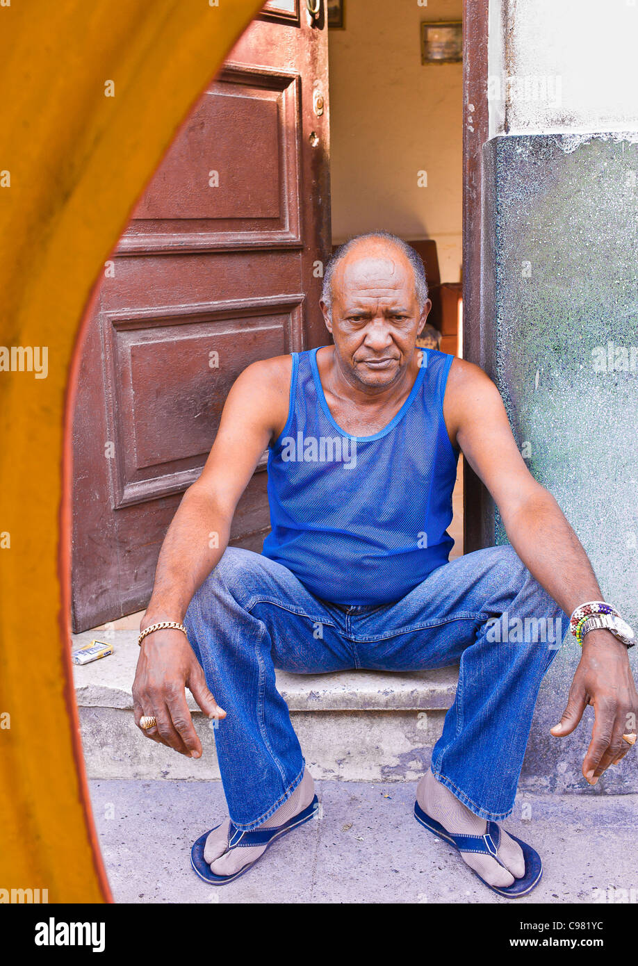 Cuban man, with a very unhappy look on his face, sitting on the step of the front door of his house in Havana, Cuba. - Stock Image