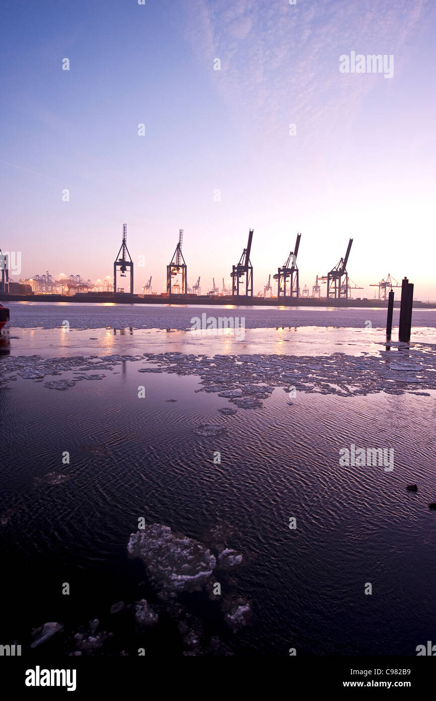 Floating ice floes in Hamburg Harbour, harbour cranes, in the evening, Hamburg, Germany, Europe - Stock Image