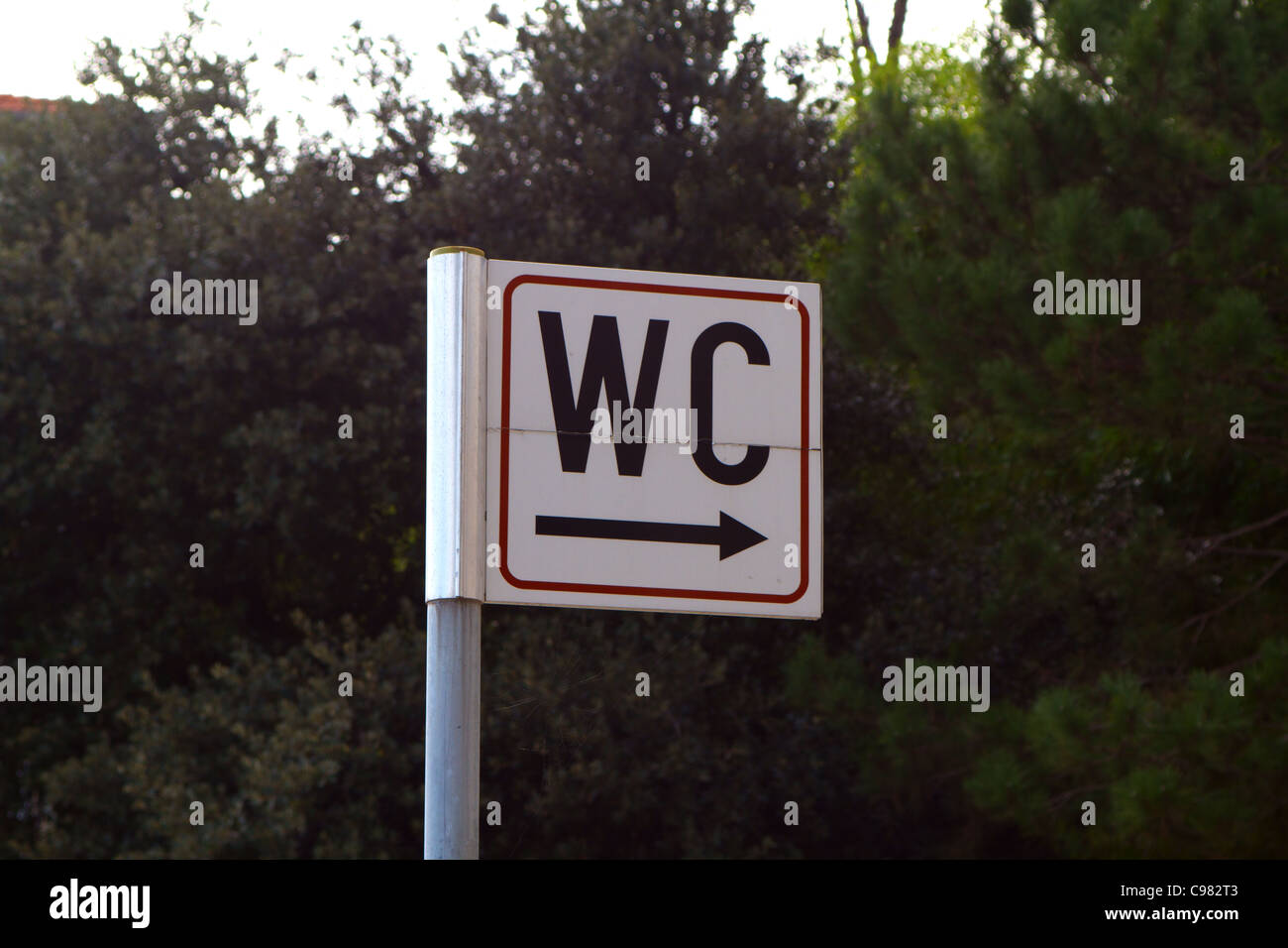 Sign for toilet - WC with arrow pointing to bushes - Stock Image