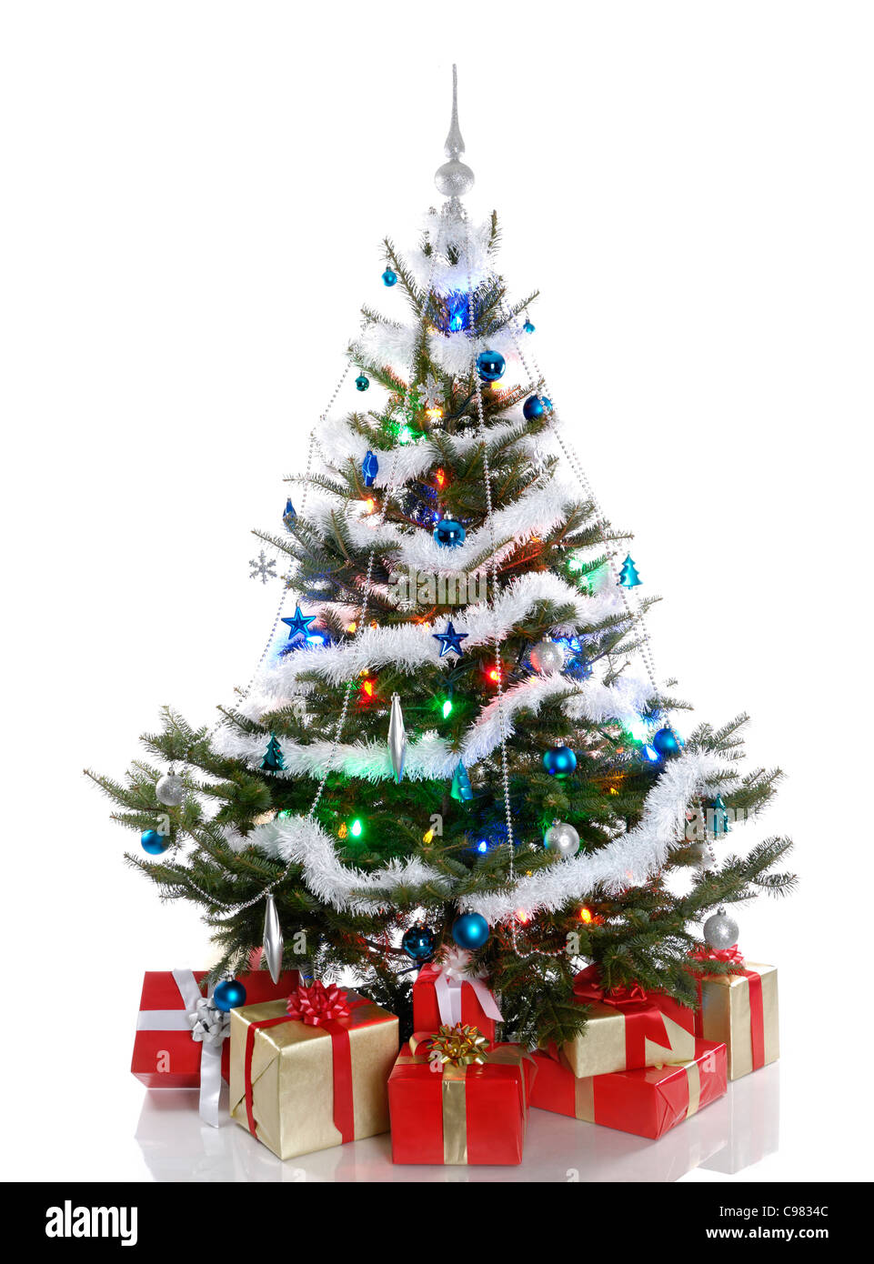 Decorated Christmas tree with gifts under it. Isolated on white background. - Stock Image