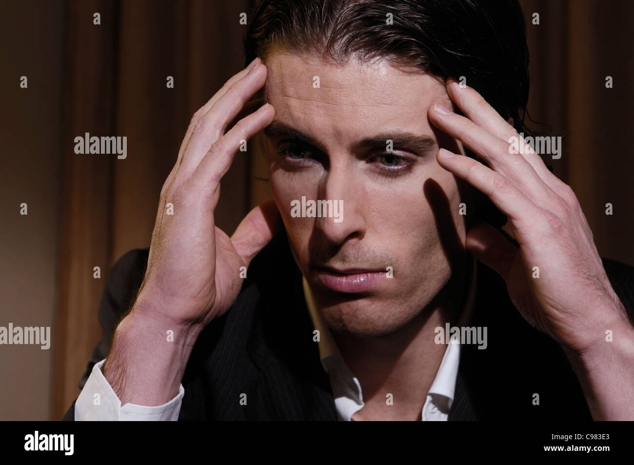 Stressed young man sitting at a desk and rubbing his temples. Closeup of face. - Stock Image