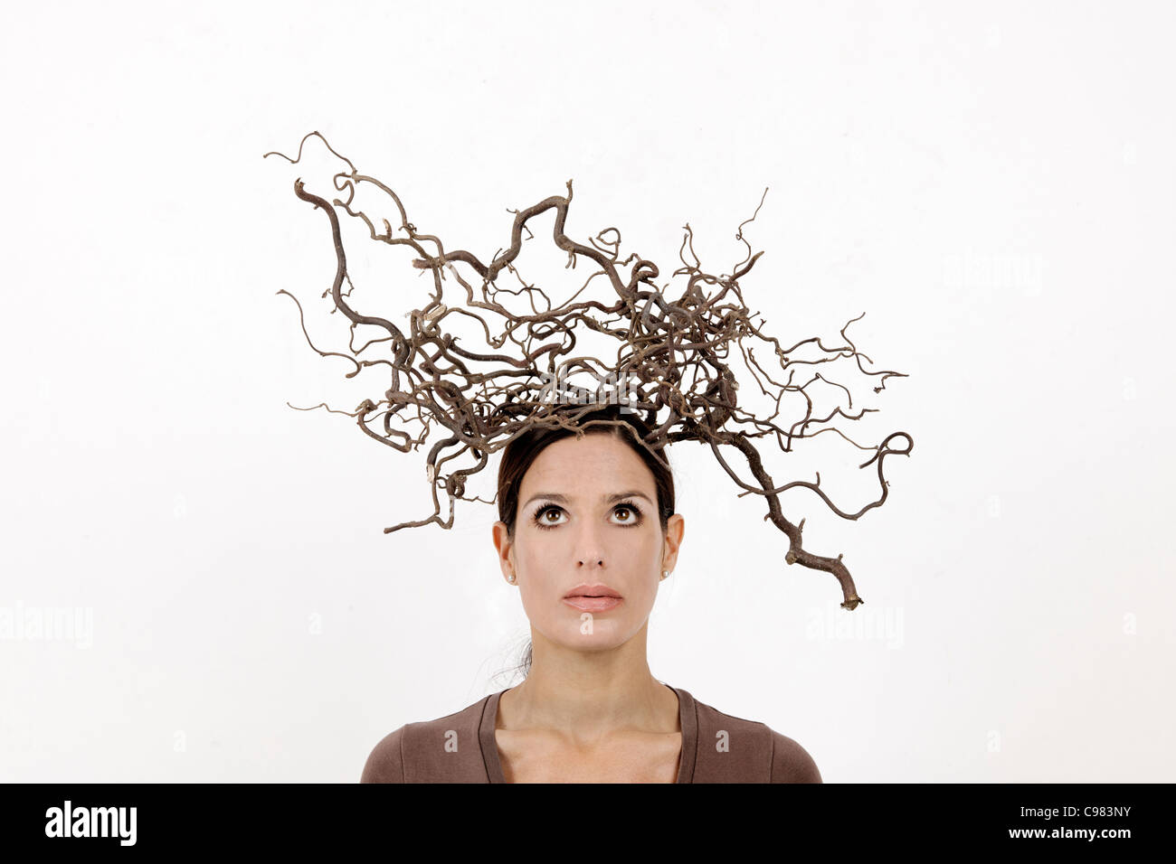 young woman with dried twigs on his head, confused, mind, insecurity, Cut out, Studio Shot - Stock Image