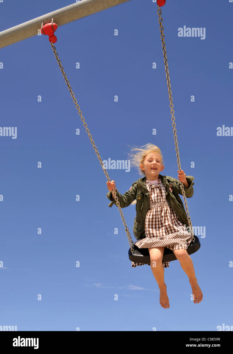 Small 6-year-old blonde girl on a playground, Germany, Europe - Stock Image