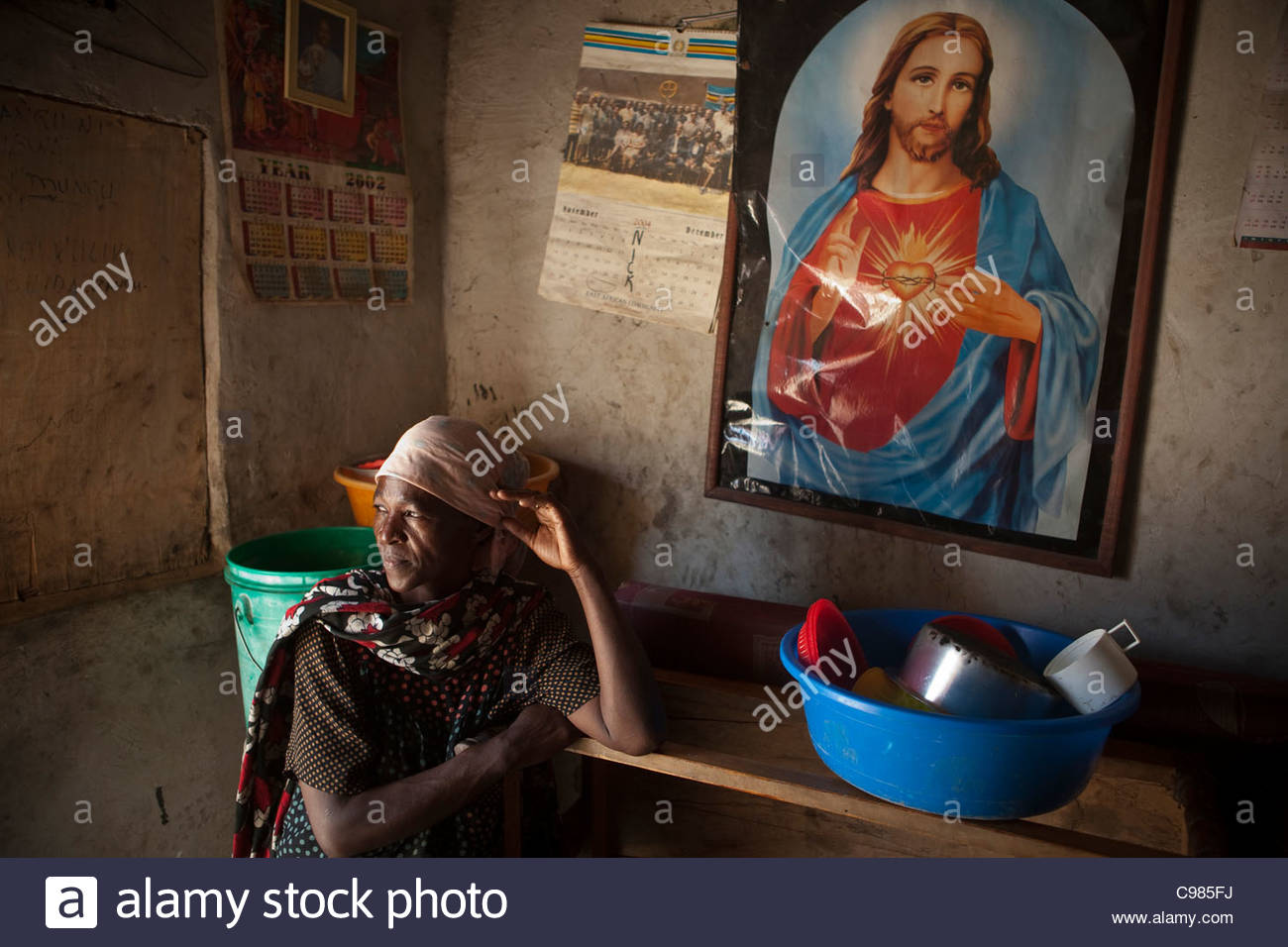 Local woman in her home in front of a picture of Jesus - Stock Image