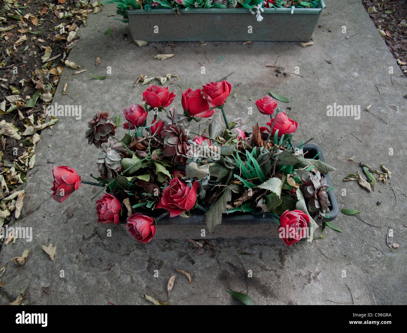 Faded red plastic flowers on grave. - Stock Image
