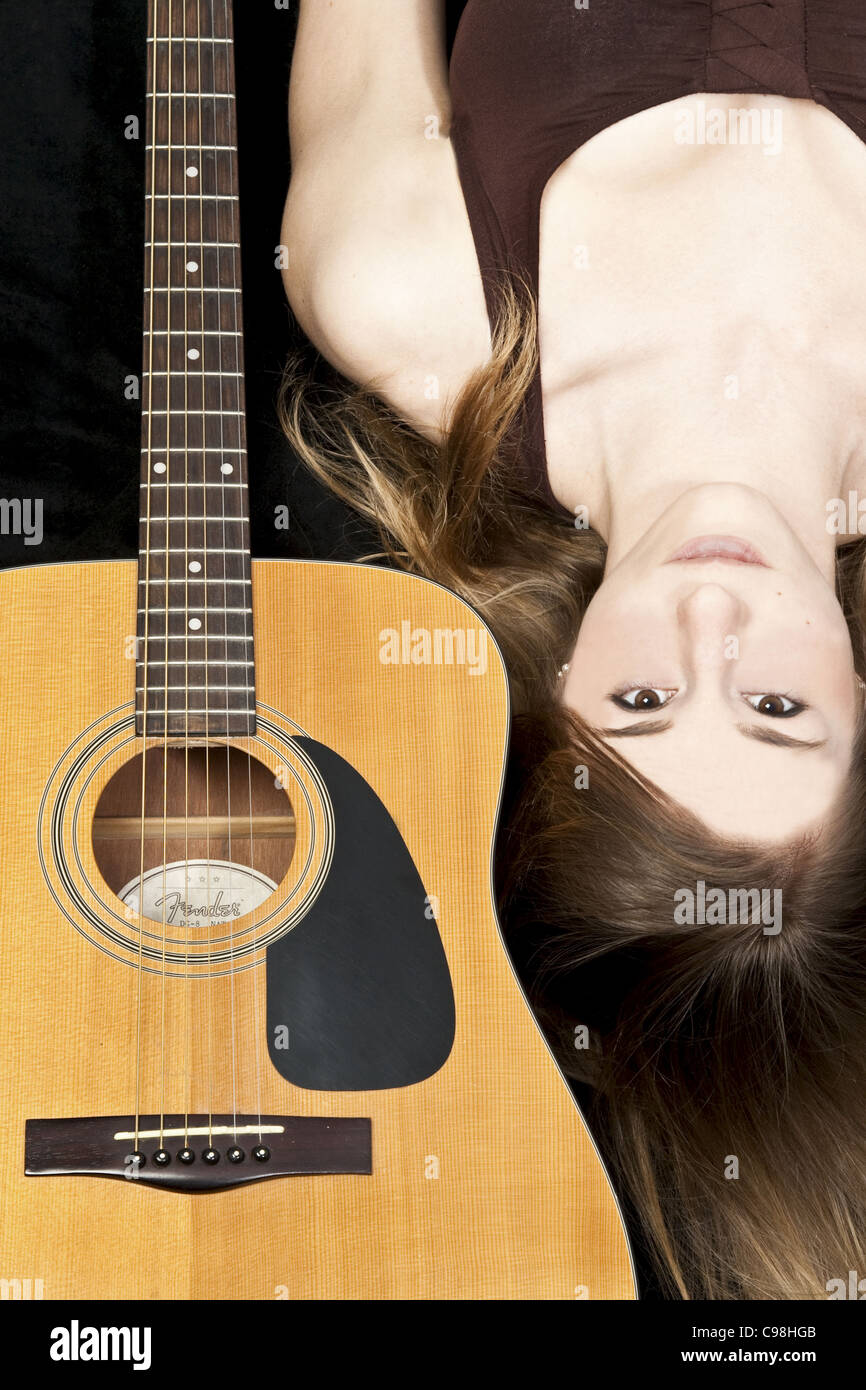 Colour Portrait of a young girl with a Fender Acoustic Guitar - Stock Image