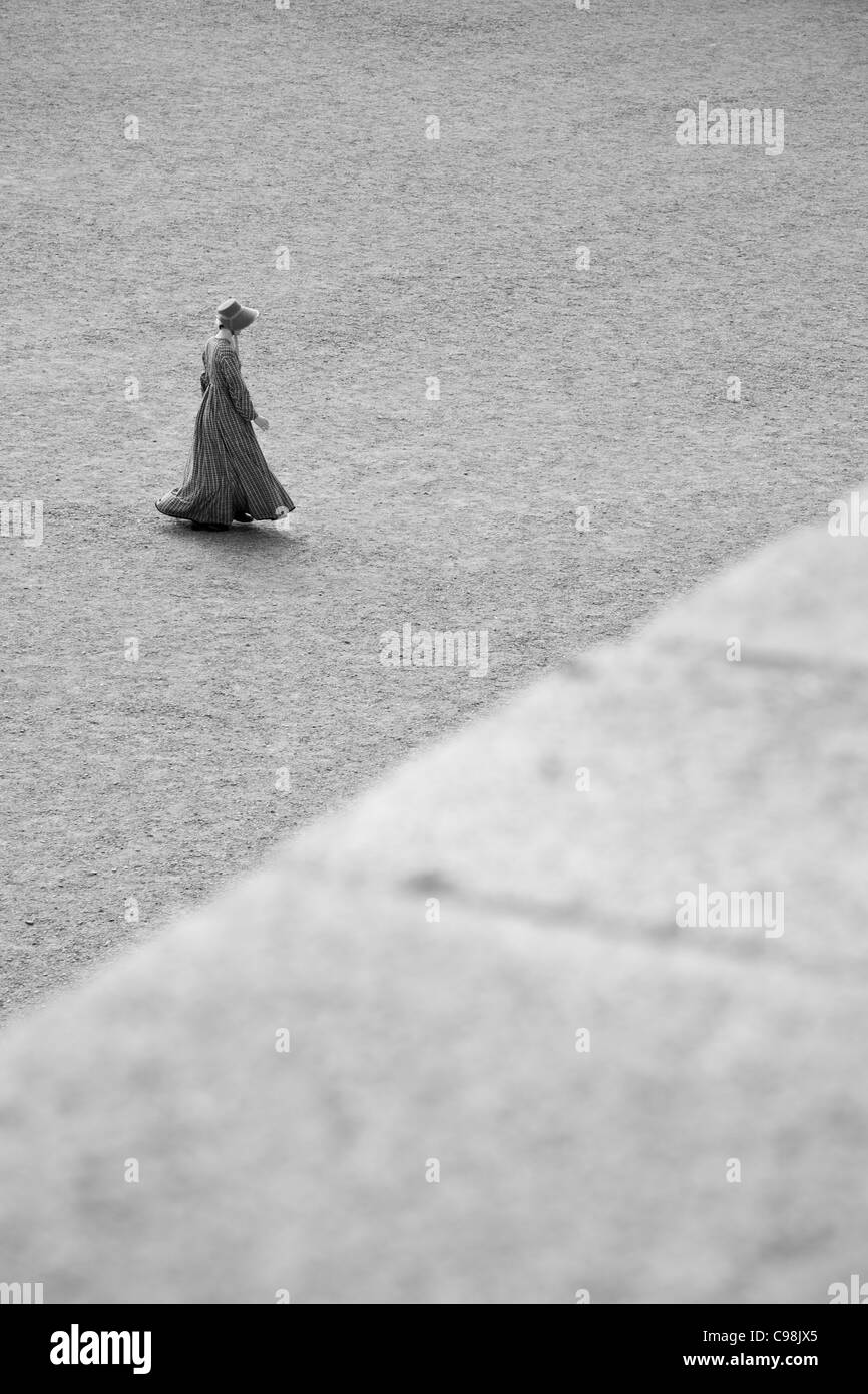 Black and white photo of a women walking across an open gravel enclosure in traditional English clothing of the - Stock Image