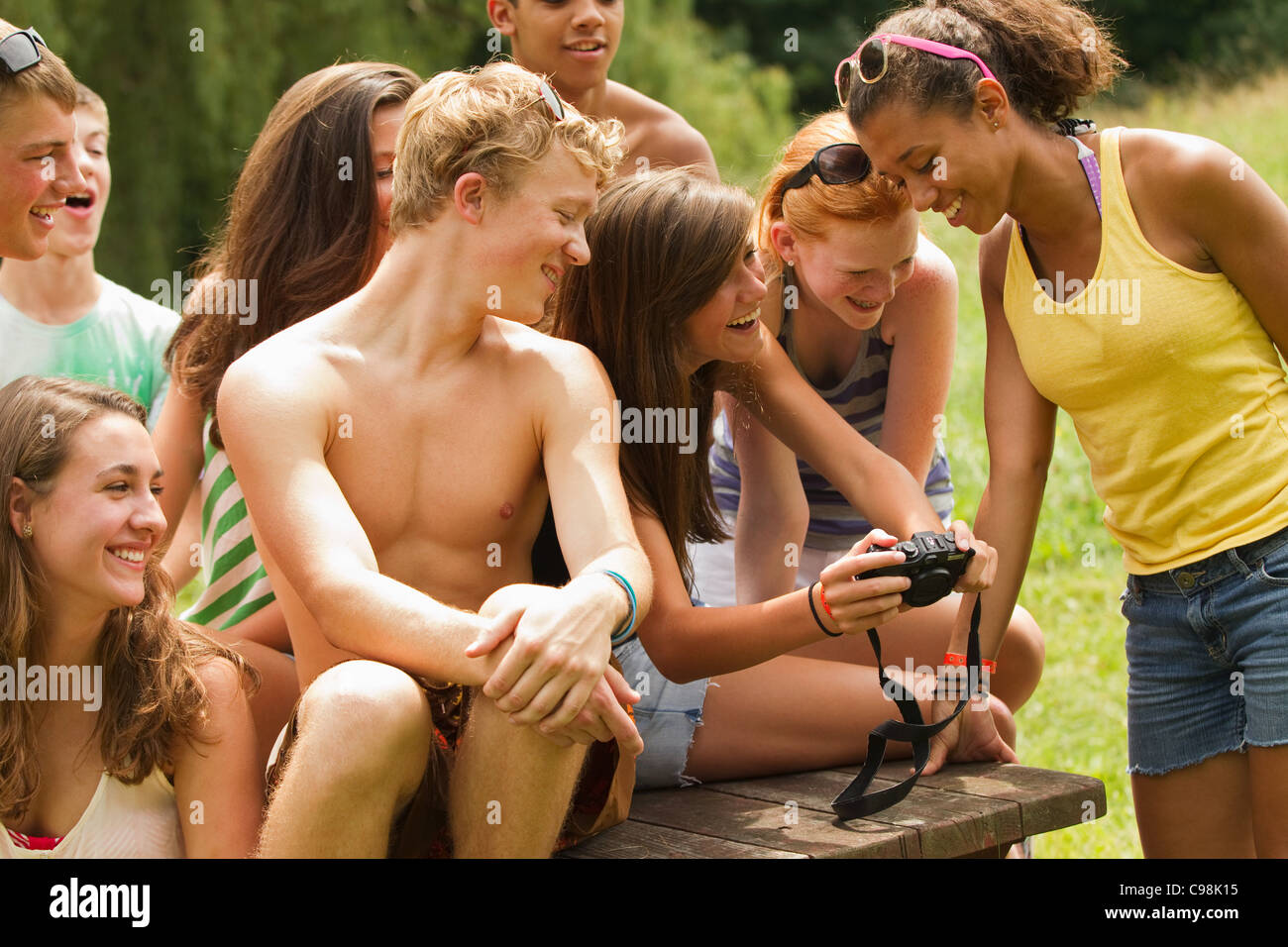 Teenagers reviewing photos together on friend's camera - Stock Image