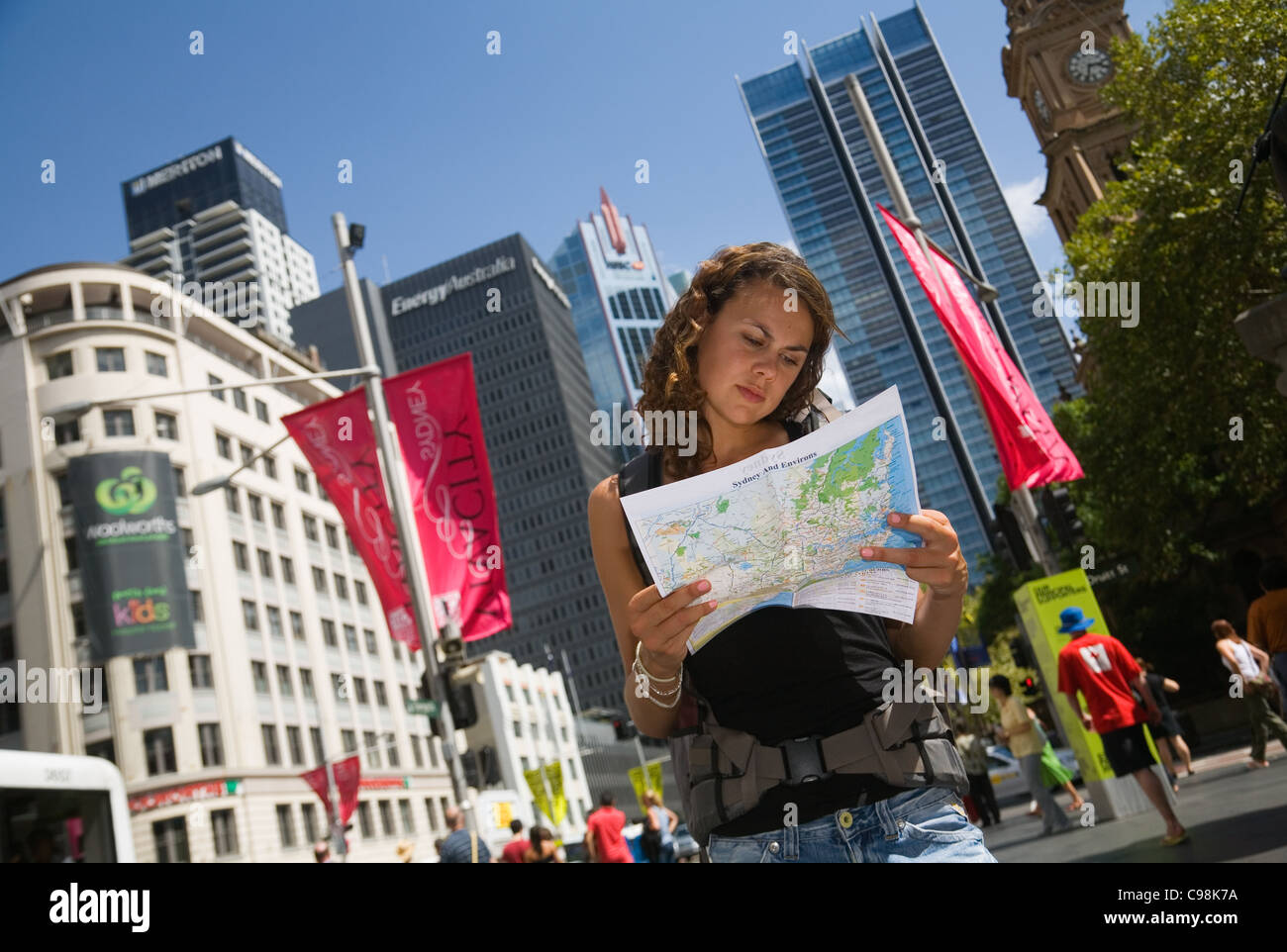 Female backpacker reading map with city skyline in background.  Sydney, New South Wales, Australia - Stock Image