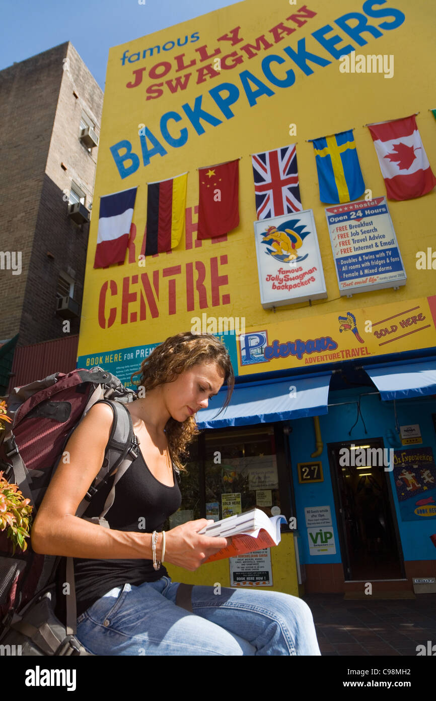 Young woman reading guidebook outside a backpacker hostel. Kings Cross, Sydney, New South Wales, Australia - Stock Image