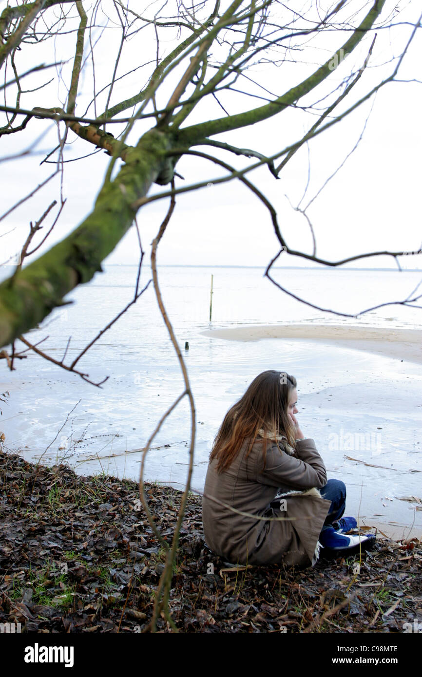Young woman depressed at water line outside in winter coat, could be depressed young woman because of winter depression - Stock Image