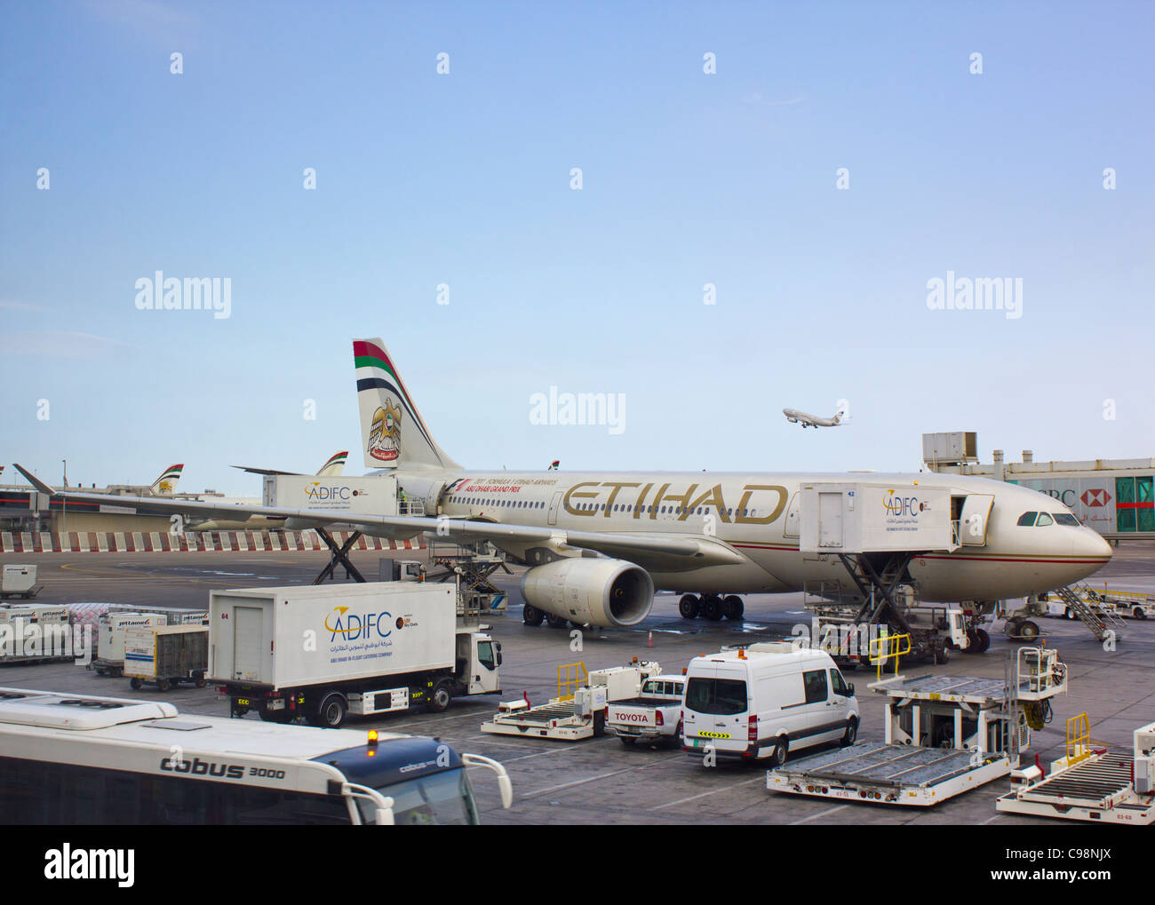 Airbus A330-200 Etihad airways plane at Terminal 1, Abu Dhabi airport, United Arab Emirates; another Etihad plane - Stock Image