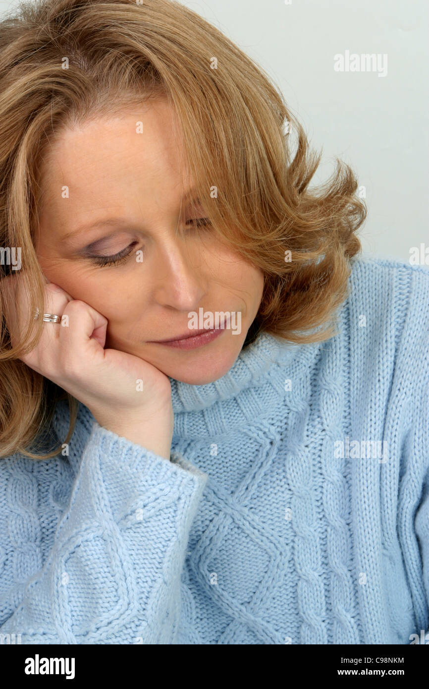 Adult woman alone looking down, mature woman alone sadness - Stock Image