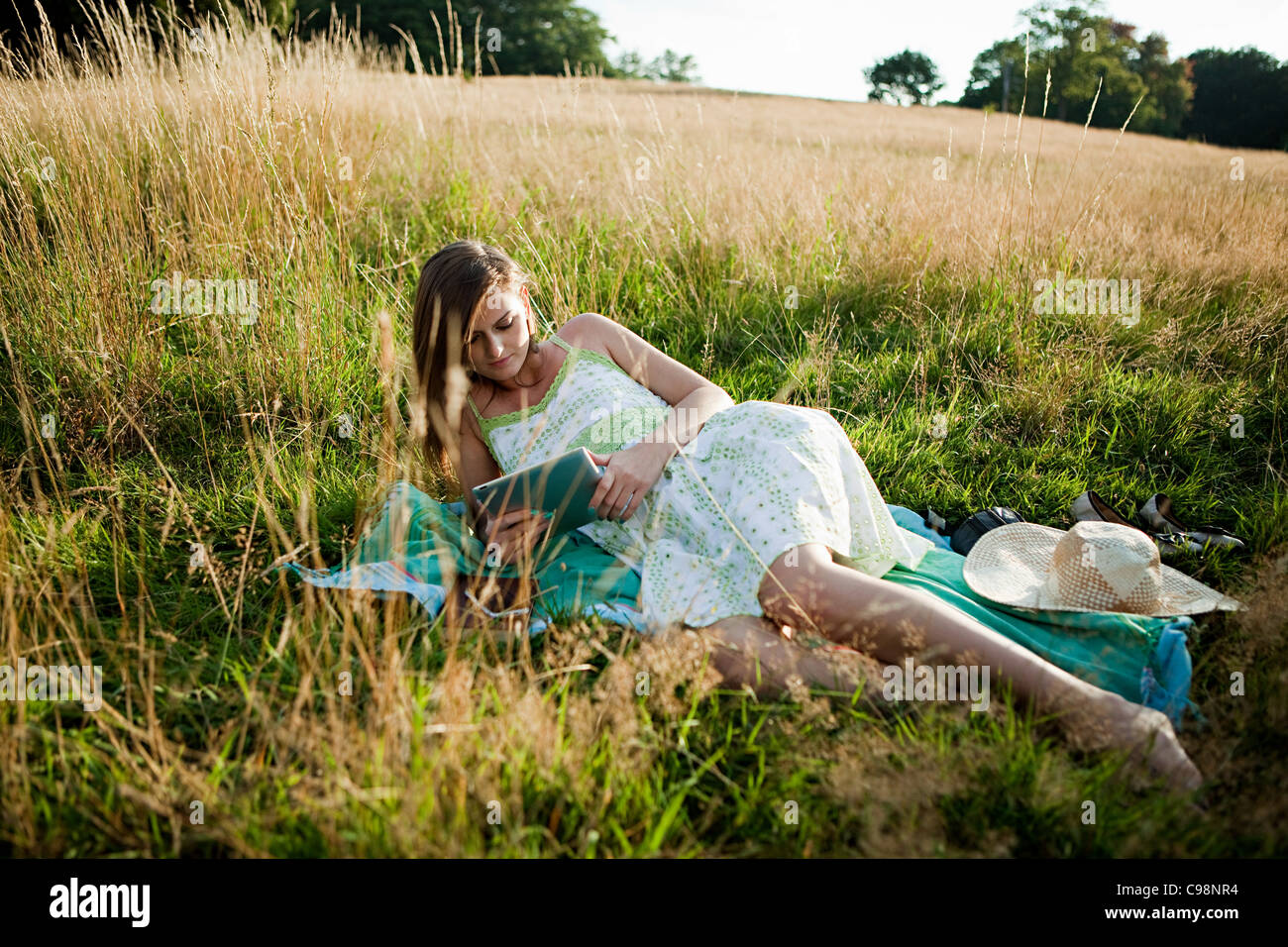 Young woman lying on side field looking hand held device - Stock Image