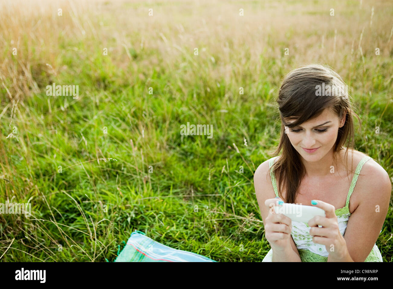 Young woman looking hand held device field - Stock Image