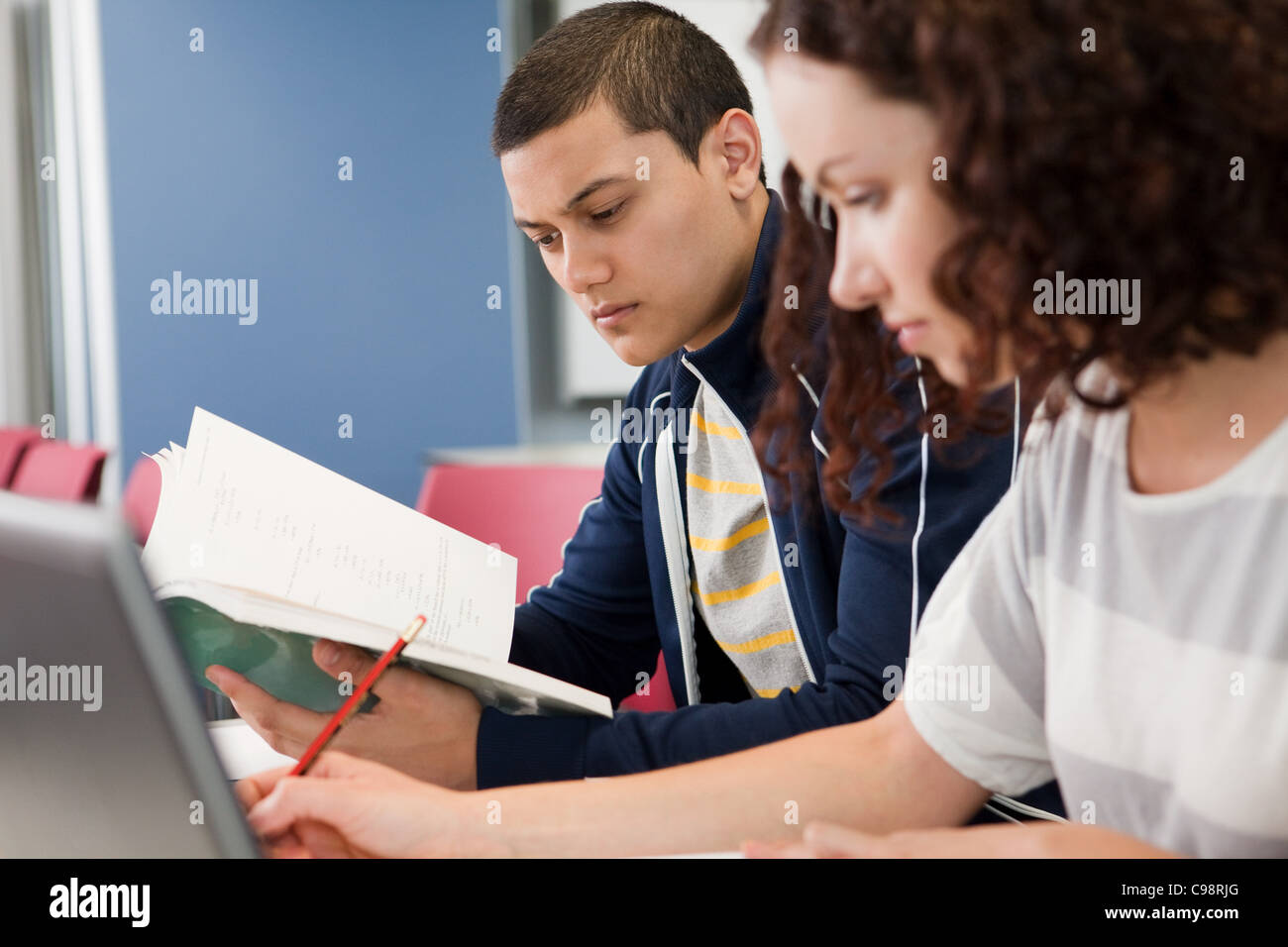 University student studying textbook class - Stock Image