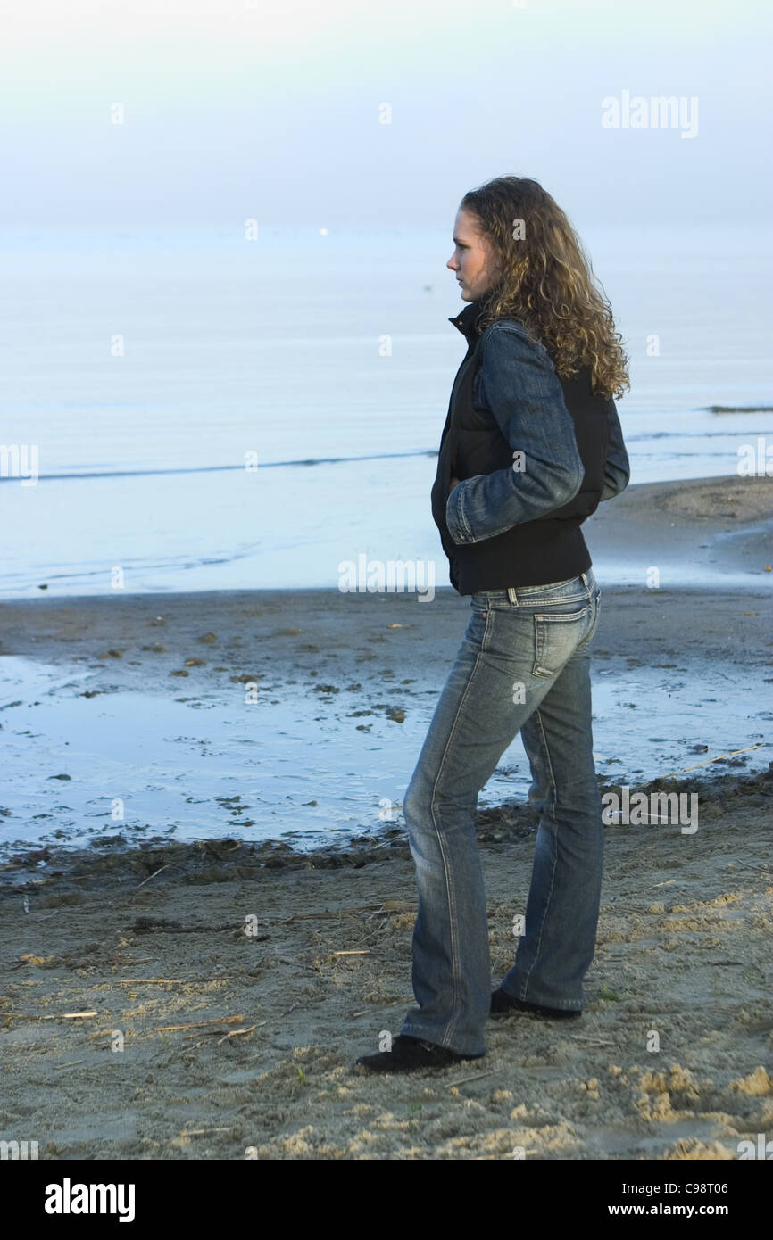 Side view pensive woman standing at shore line - Stock Image