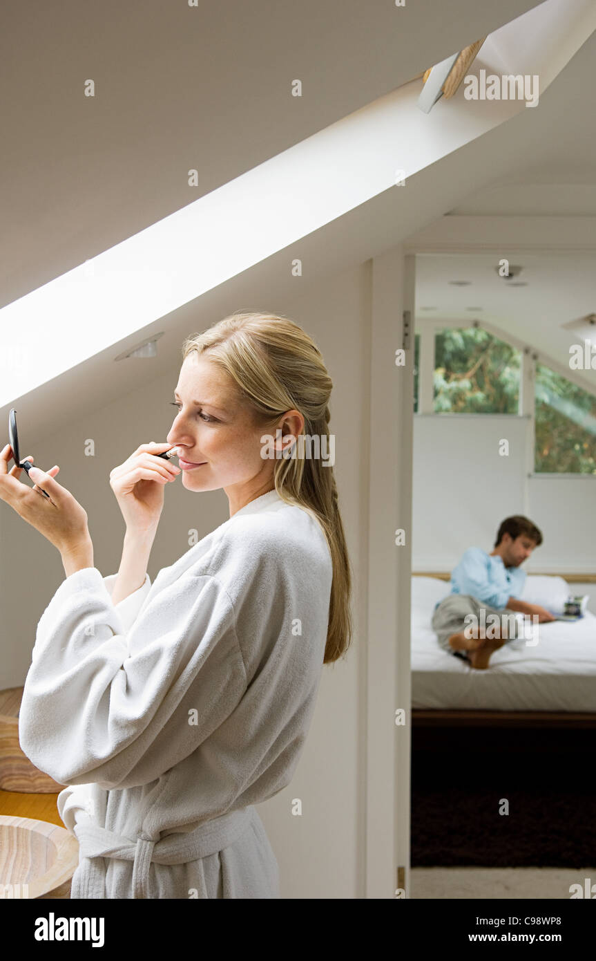 Young woman applying make up in bathroom - Stock Image