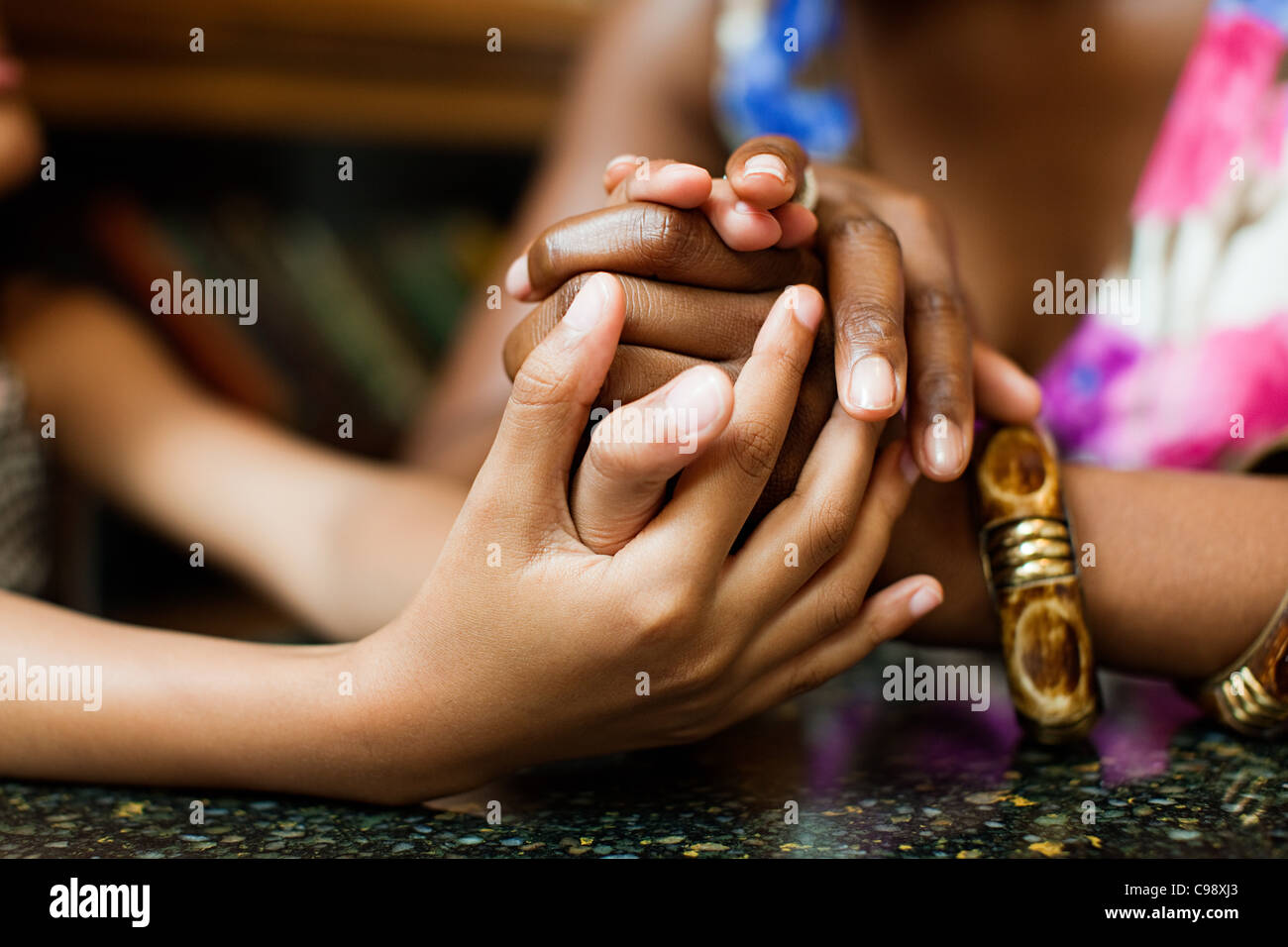 Mother and daughter holding hands in cafe - Stock Image