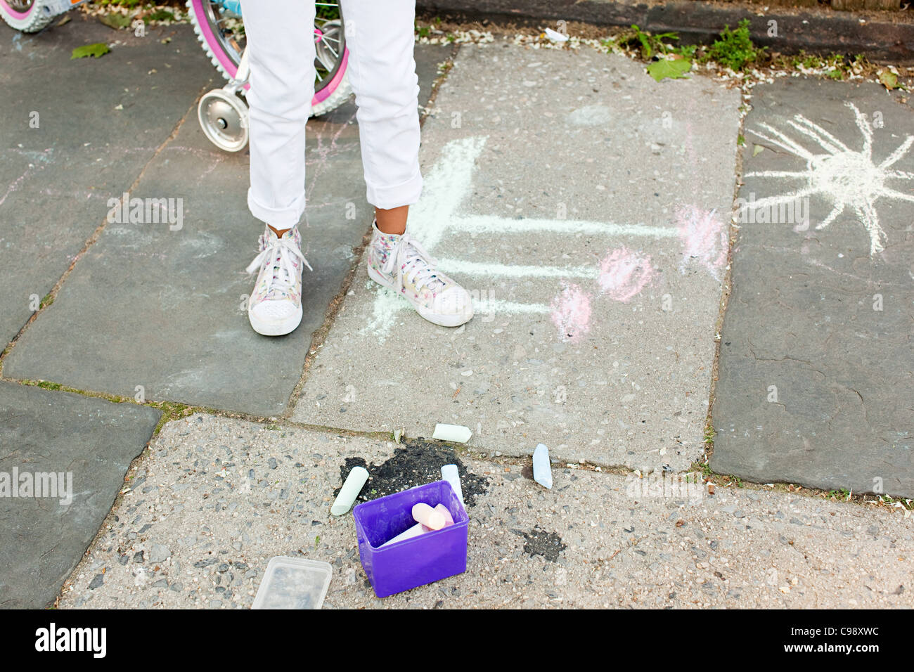 Girl standing by chalk drawing on sidewalk Stock Photo
