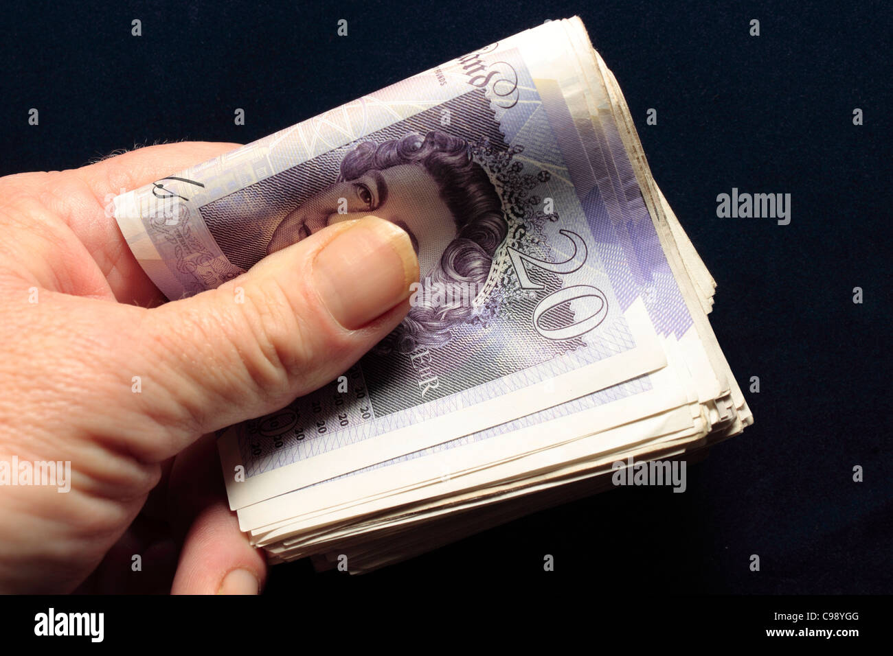 A Wad of £20 Notes folded held in hand between thumb and fingers - Stock Image