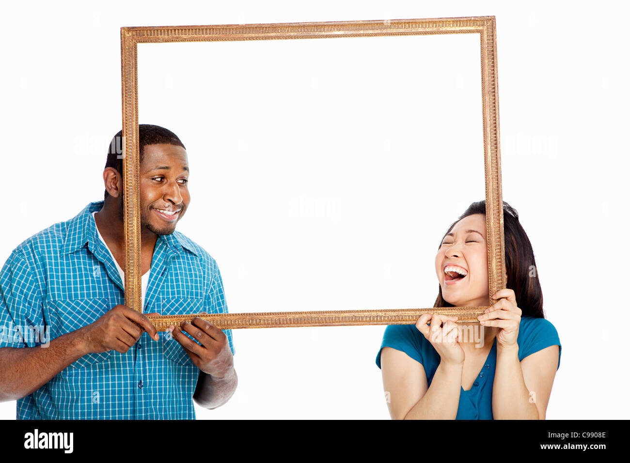 Mixed race couple holding picture frame against white background Stock Photo
