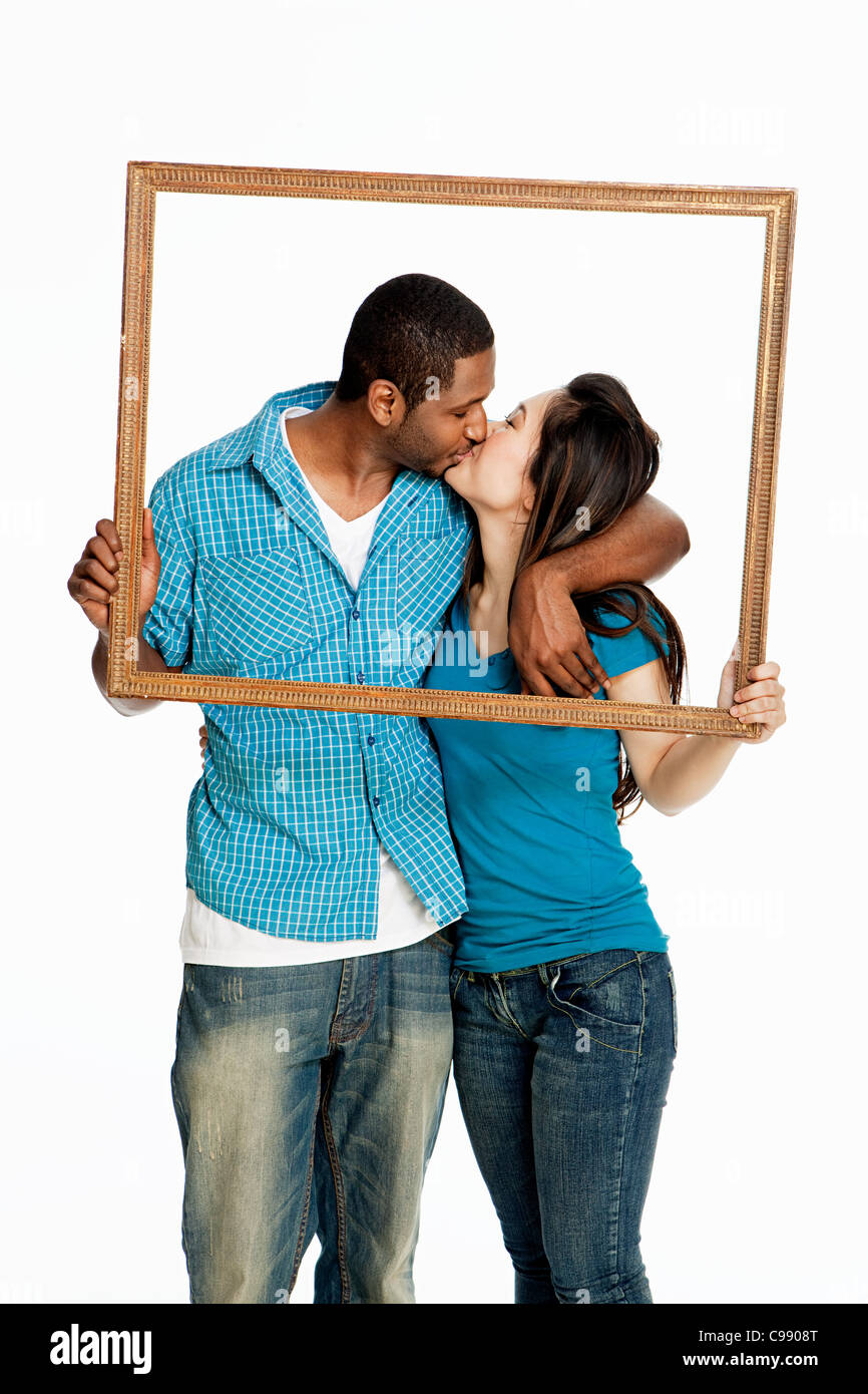 Mixed race couple kissing inside picture frame against white background - Stock Image