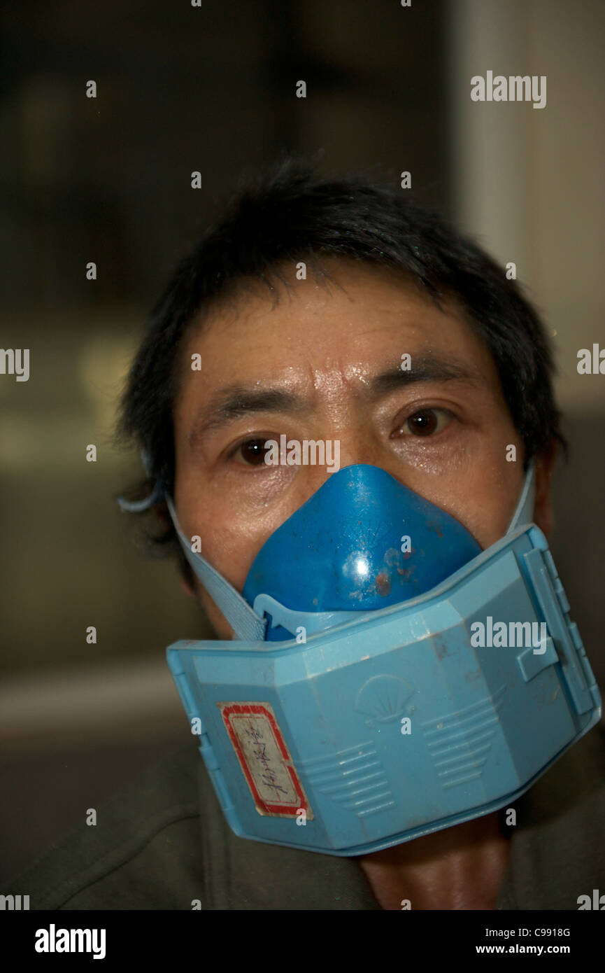 A Chinese worker with a mask working at a fluorescent powder factory in Ninghai, Zhejiang, China. 11-Nov-2011 - Stock Image