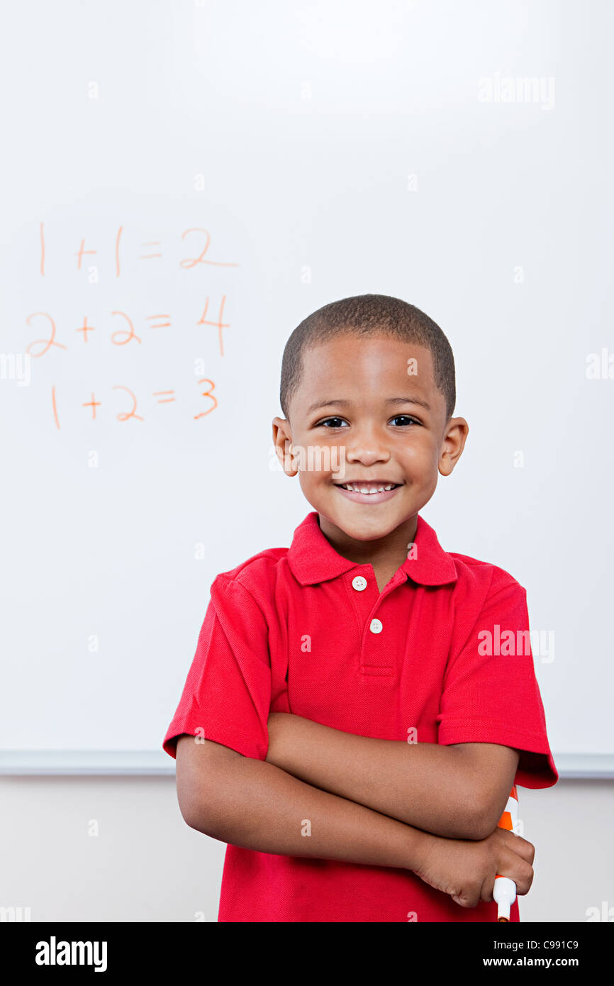 Happy schoolboy in front of mathematics on whiteboard - Stock Image