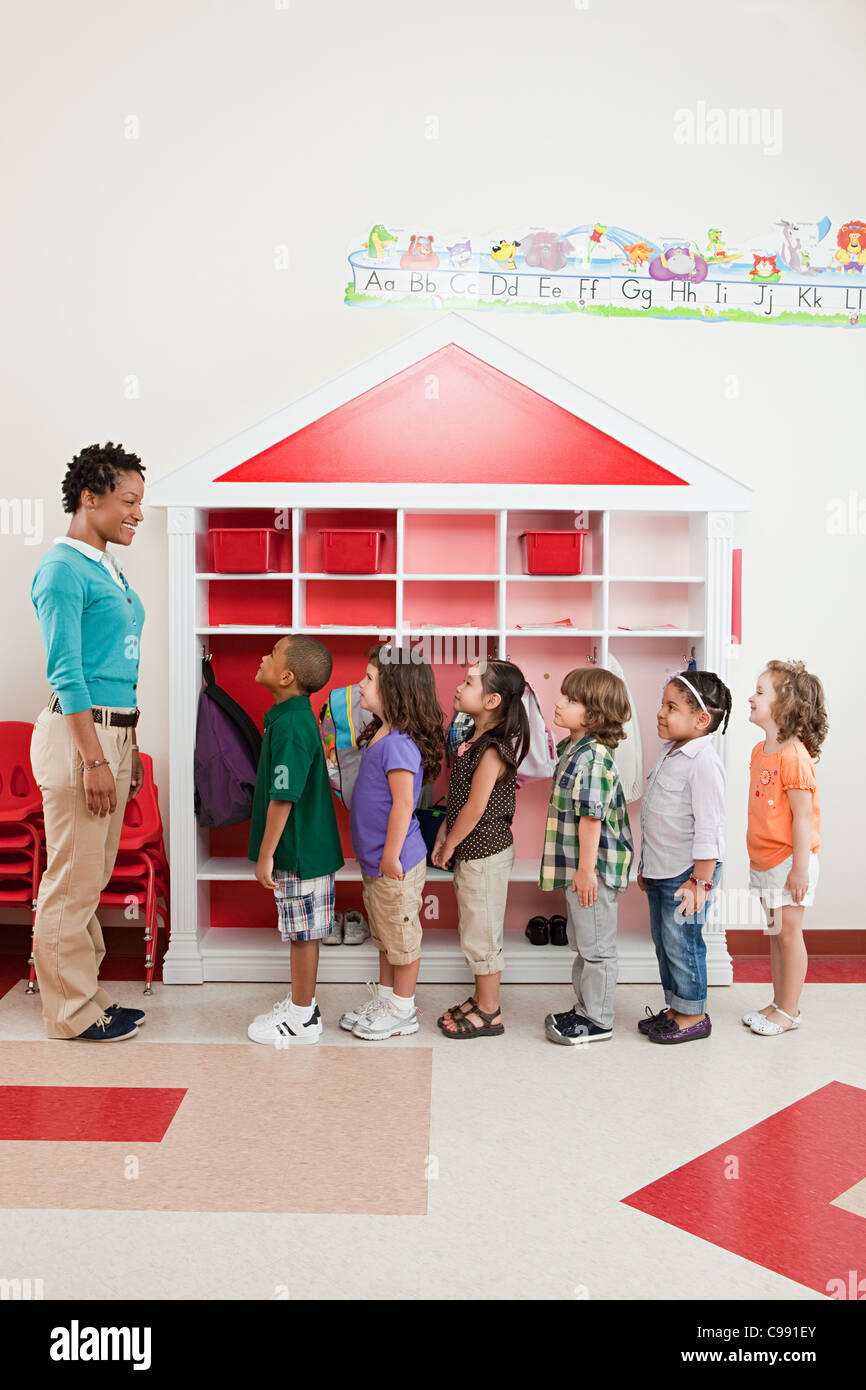 Teacher and children lining up - Stock Image