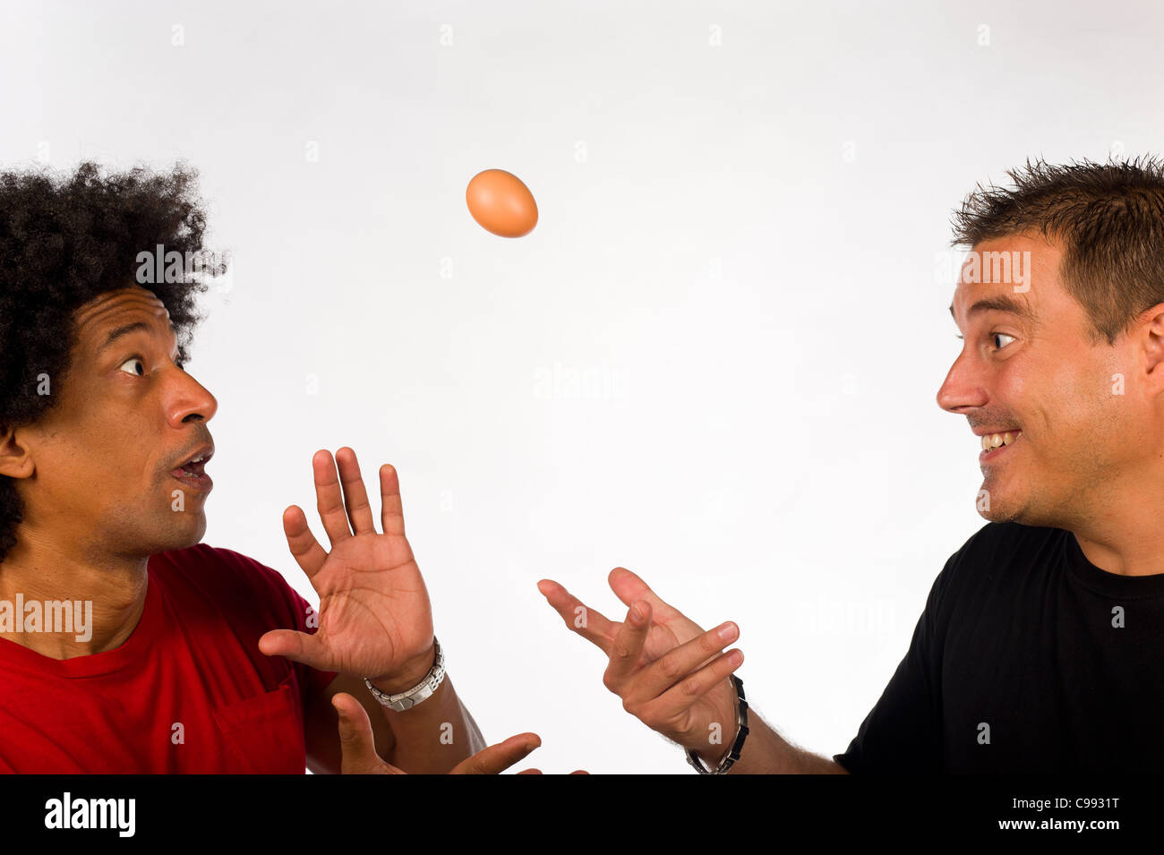 Two guys fooling around with an uncooked egg - Stock Image
