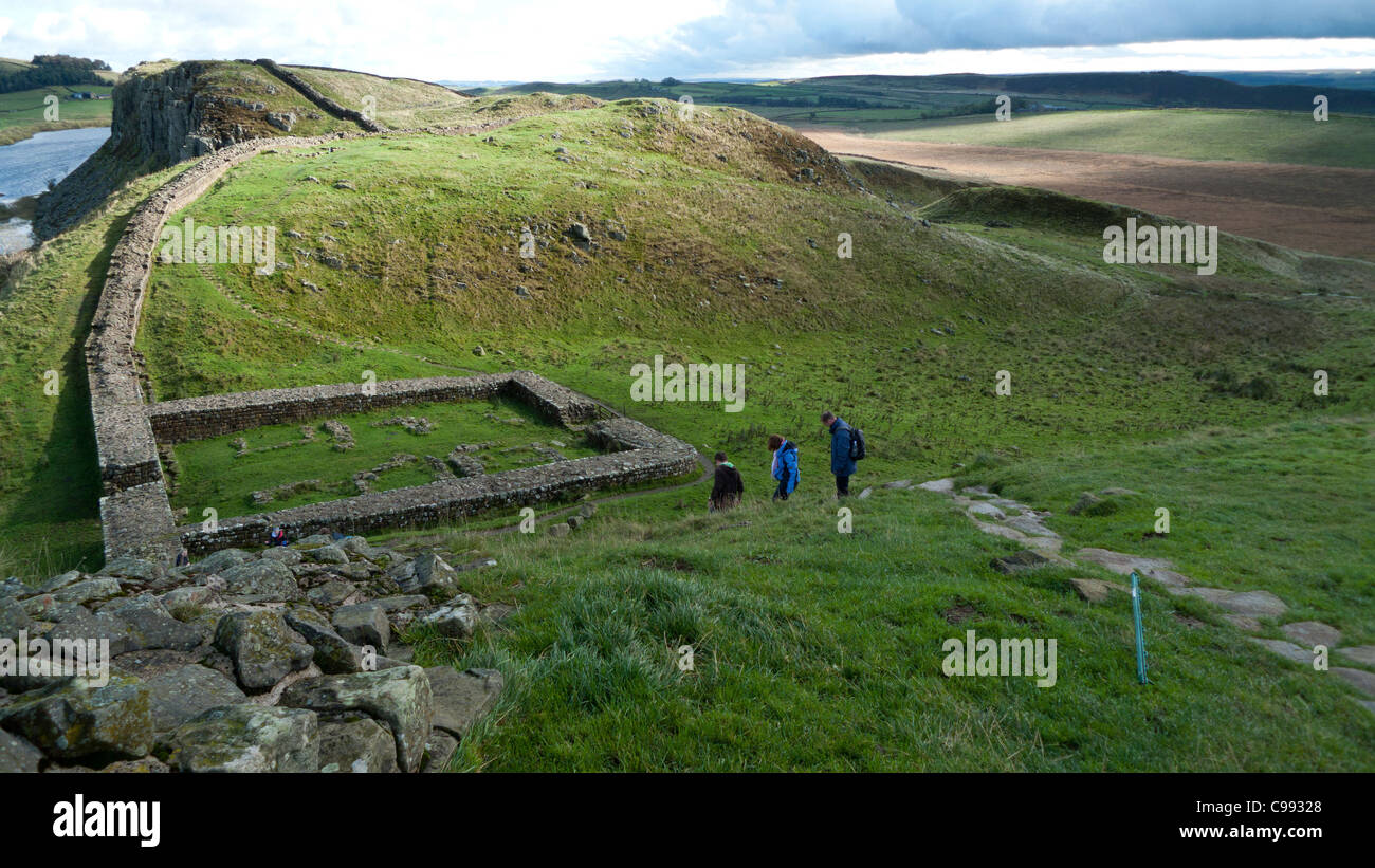 A group of walkers walking  Hadrians Wall heading east to Housesteads along The World Heritage Site in Northumberland - Stock Image