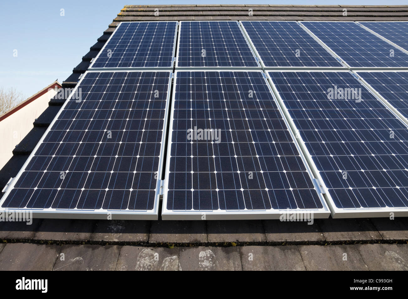 UK, Britain. Solar panels on a house roof with blue sky. - Stock Image