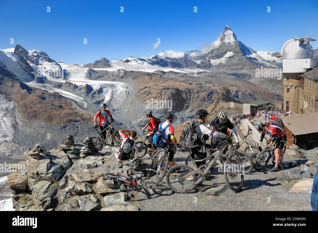 Moutain bikers about to descend from Gornegrat, 3,089m to the village of Zermatt, Valais, Switzerland - Stock Image