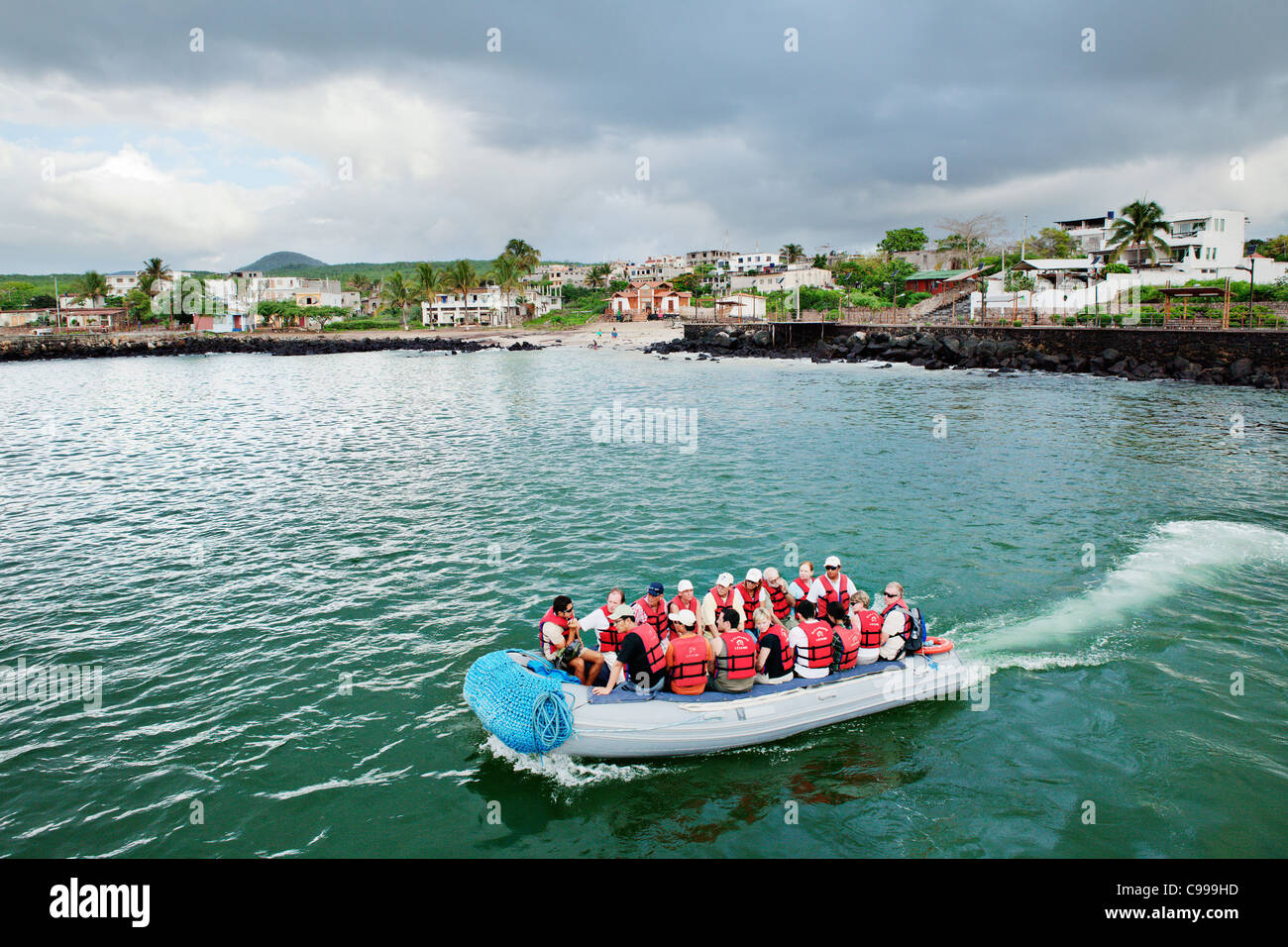 Dinghy takes tourist group back to cruise ship from Puerto Baquerizo Moreno town, San Christobal island, Galapagos, - Stock Image