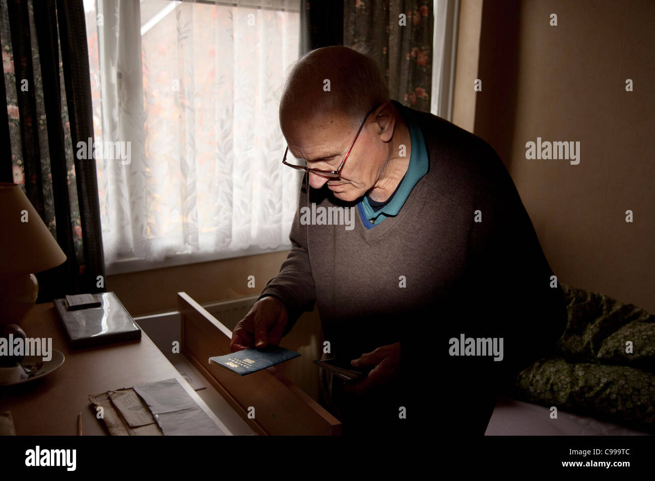 An elderly manwith dementia taking his building society book from a draw and holding it to look at in the bedroom - Stock Image