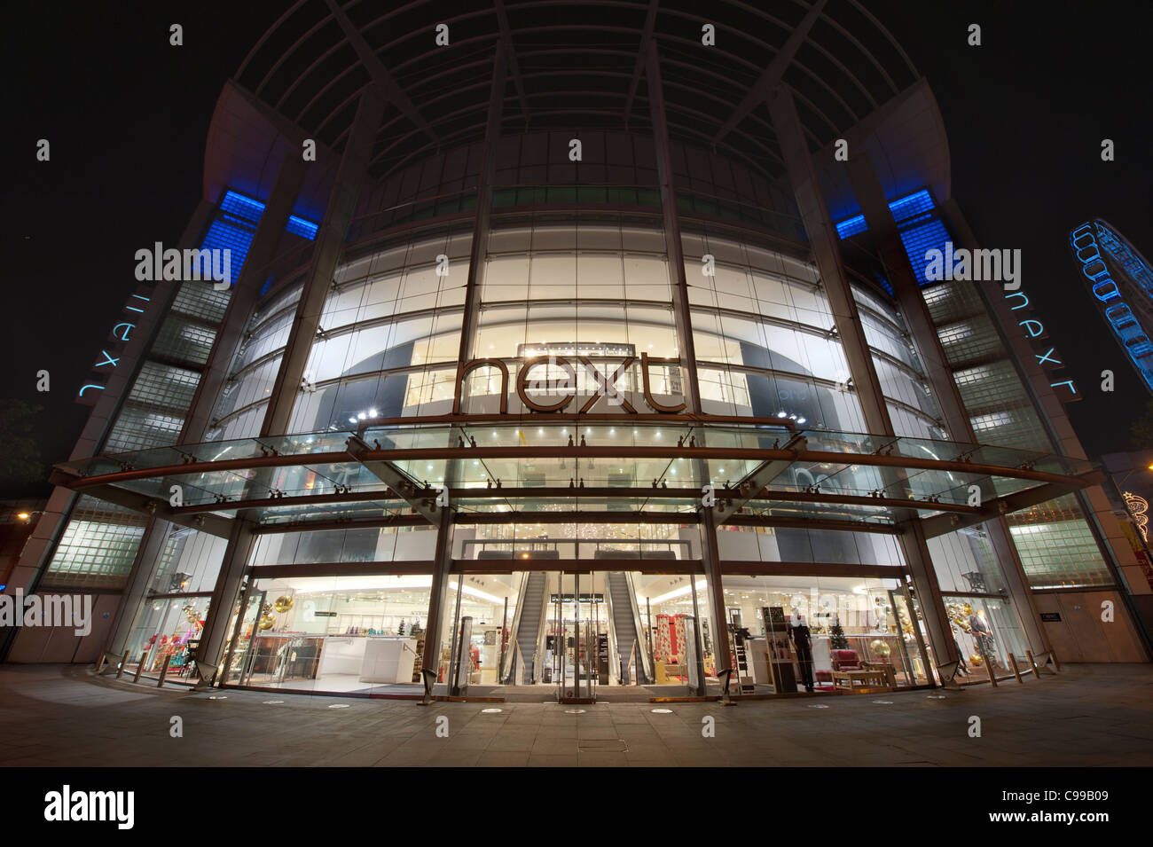 A night time shot of the entrance / storefront to the Next flagship store in Manchester with no people (Editorial - Stock Image