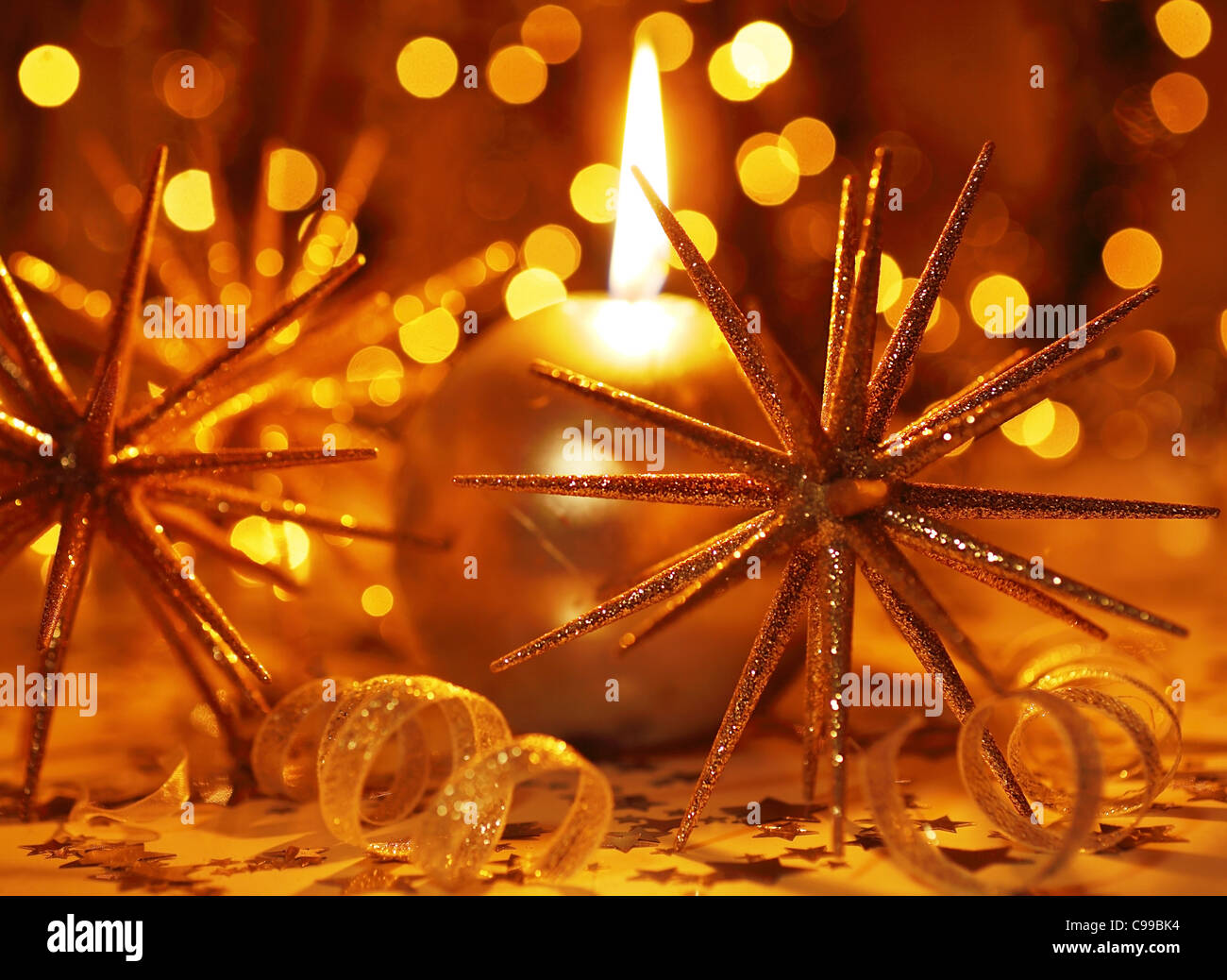 Golden holiday background with candle and Christmas tree ornament and decoration - Stock Image